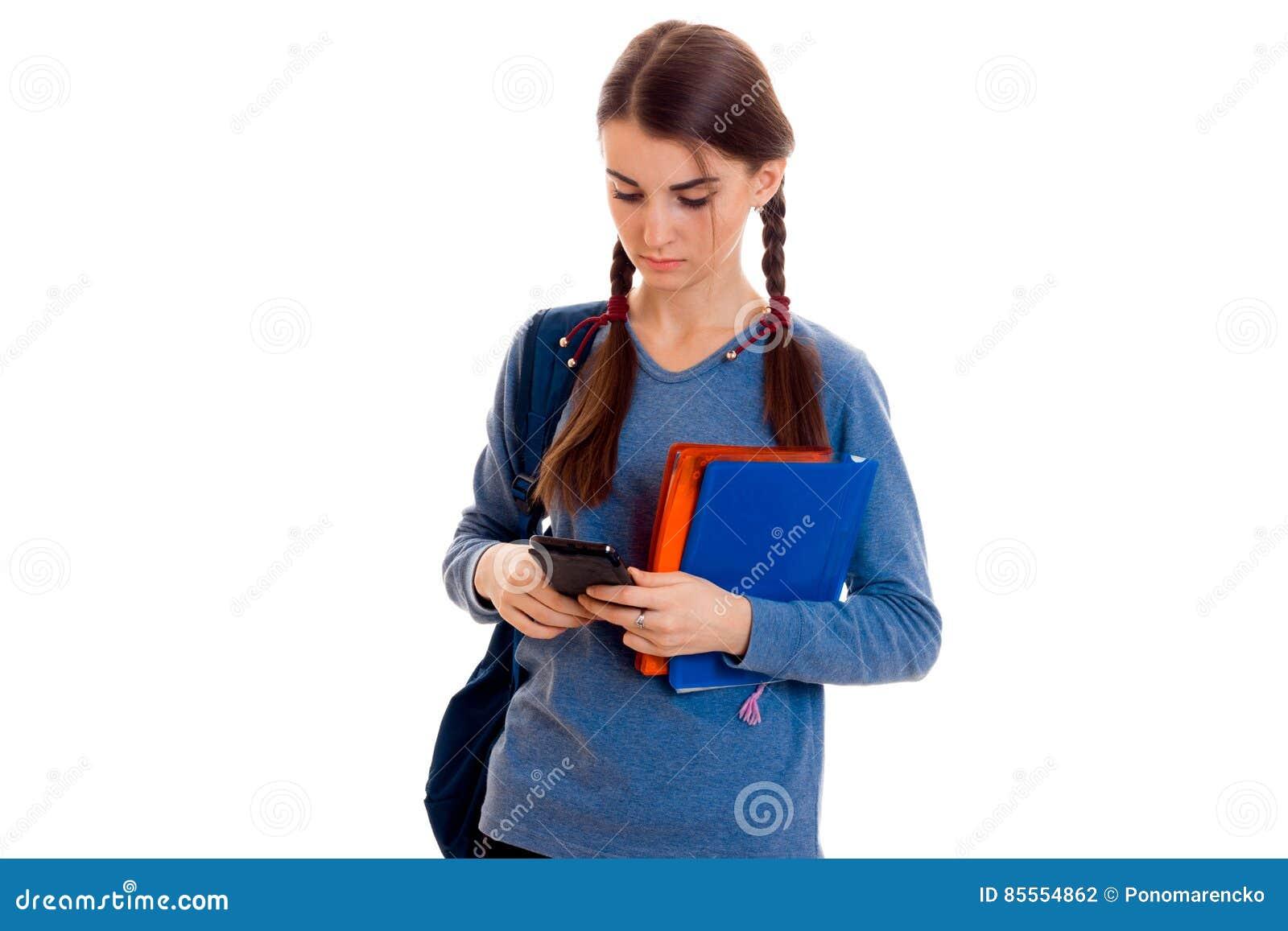 Junges schönes Studentenmädchen mit dem Rucksack, der ihren Handy und Aufstellung lokalisiert auf weißem Hintergrund im Studio be