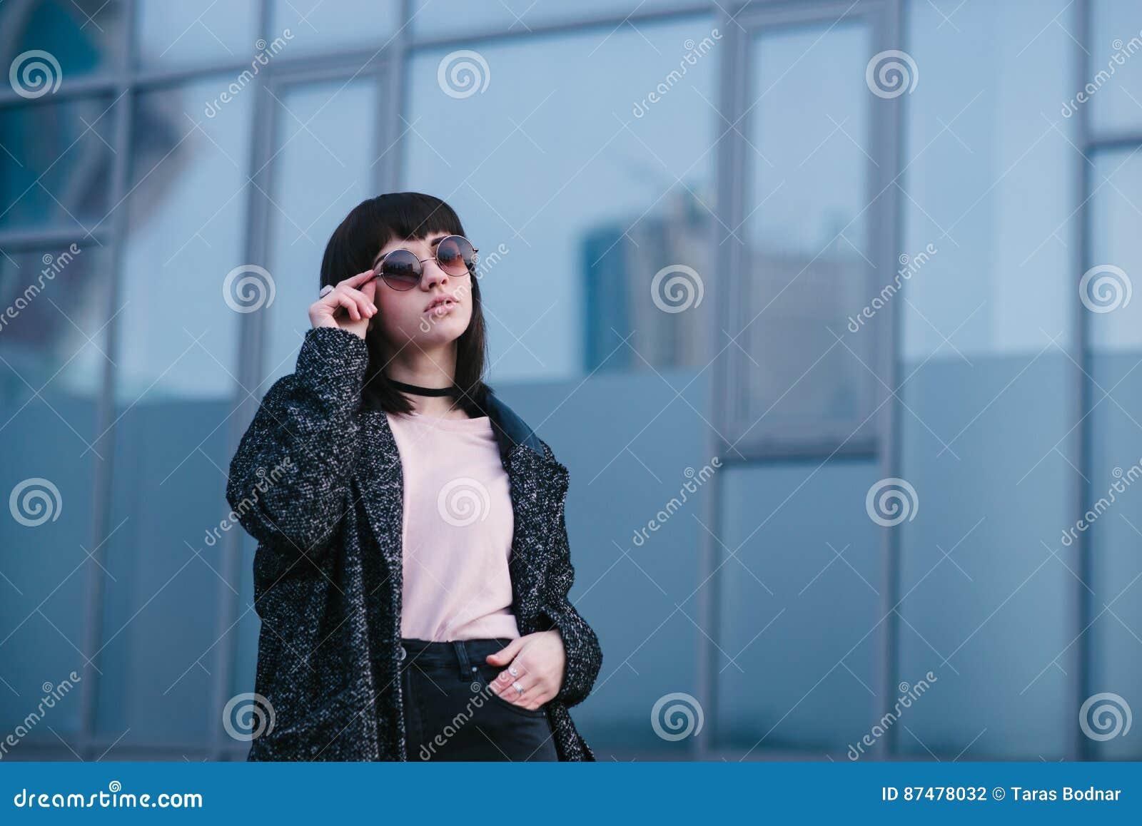 Junges, schönes und stilvolles gekleidetes Mädchen im Frühjahr, das seine Gläser und die Aufstellung auf städtischem Hintergrund