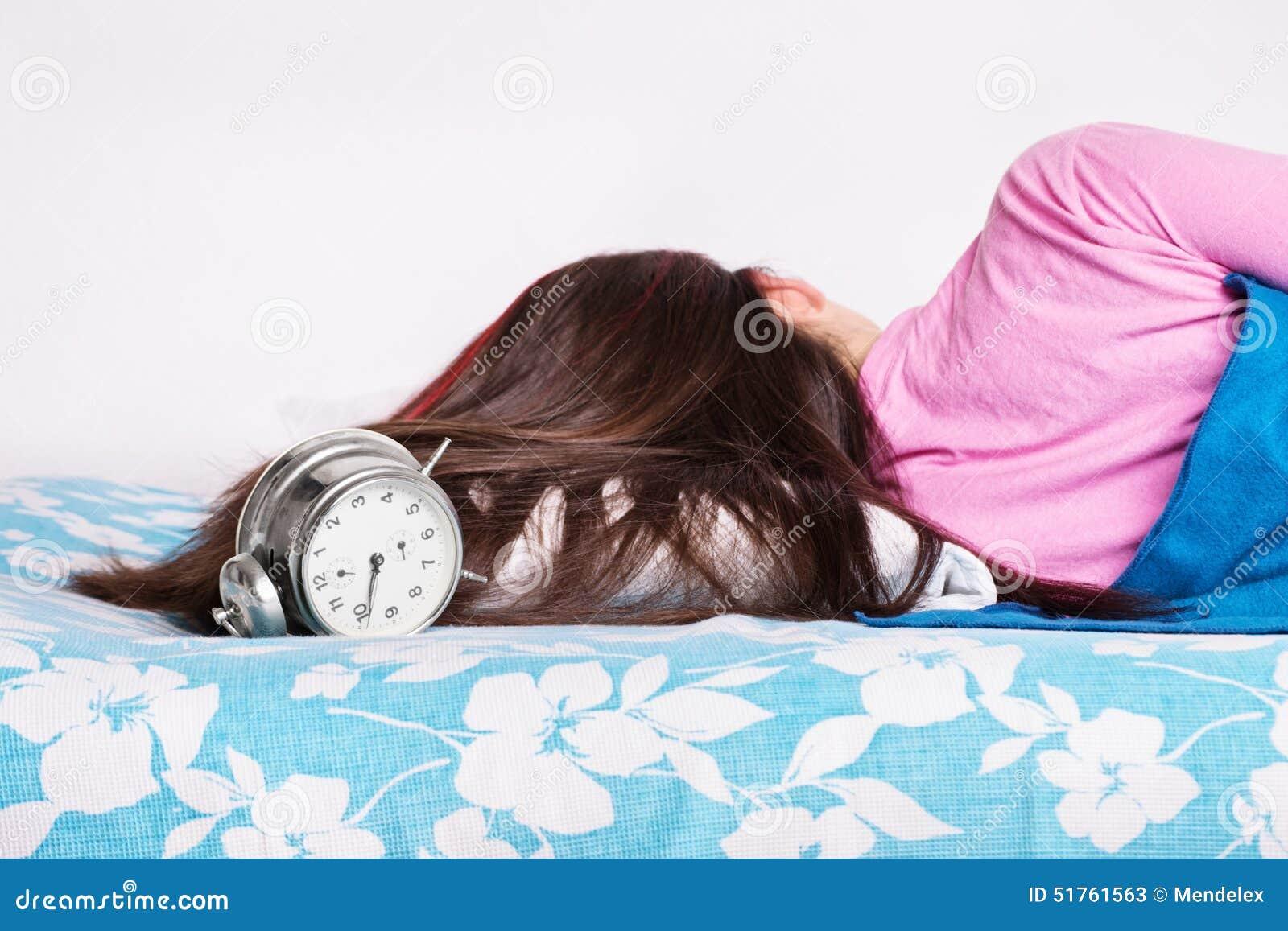 Junges schlafendes Mädchen, während die Uhr schellt