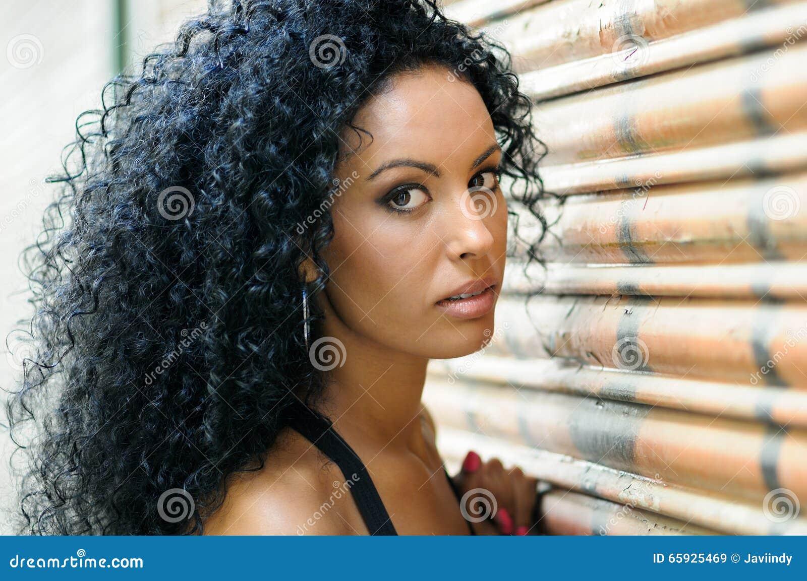Junges schwarzes Mädchen, Afrofrisur, mit dem sehr gelockten Haar