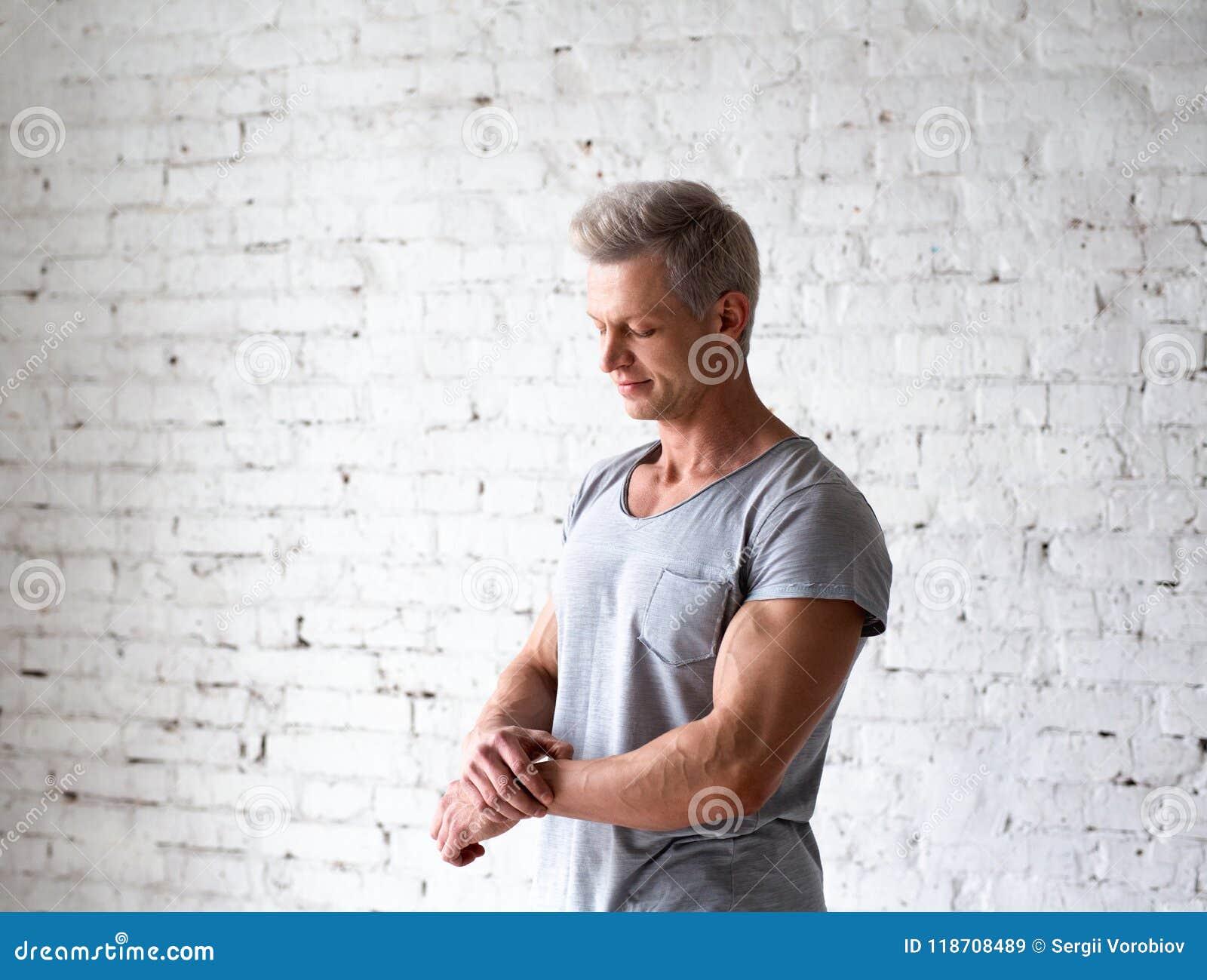 Junges sexy Mannbodybuilderathleten-Studioporträt im Dachboden auf dem Hintergrund der weißen Backsteinmauer Hübsches Kerlmodell