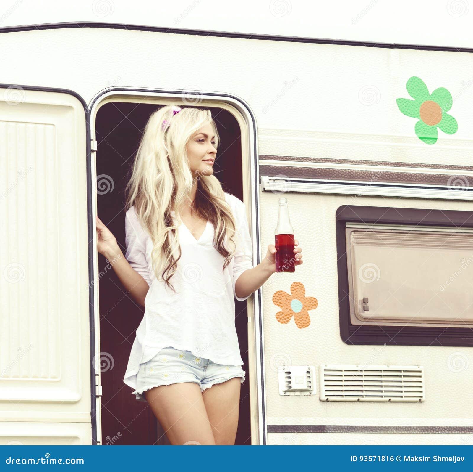 Junges und schönes Hippiemädchen, das in trailer's Tür steht Hol