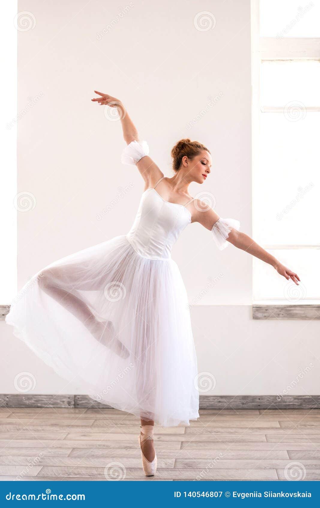 Junges würdevolles Ballerinatanzen auf weißem Studio