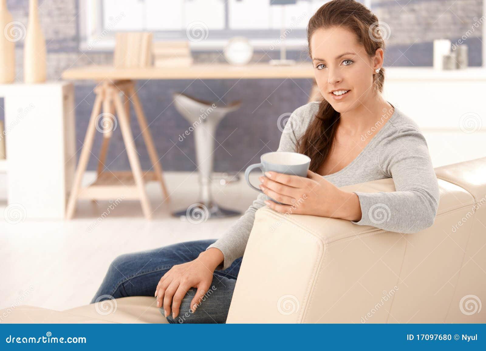 Junges weibliches Sitzen auf dem trinkenden Teelächeln des Sofas