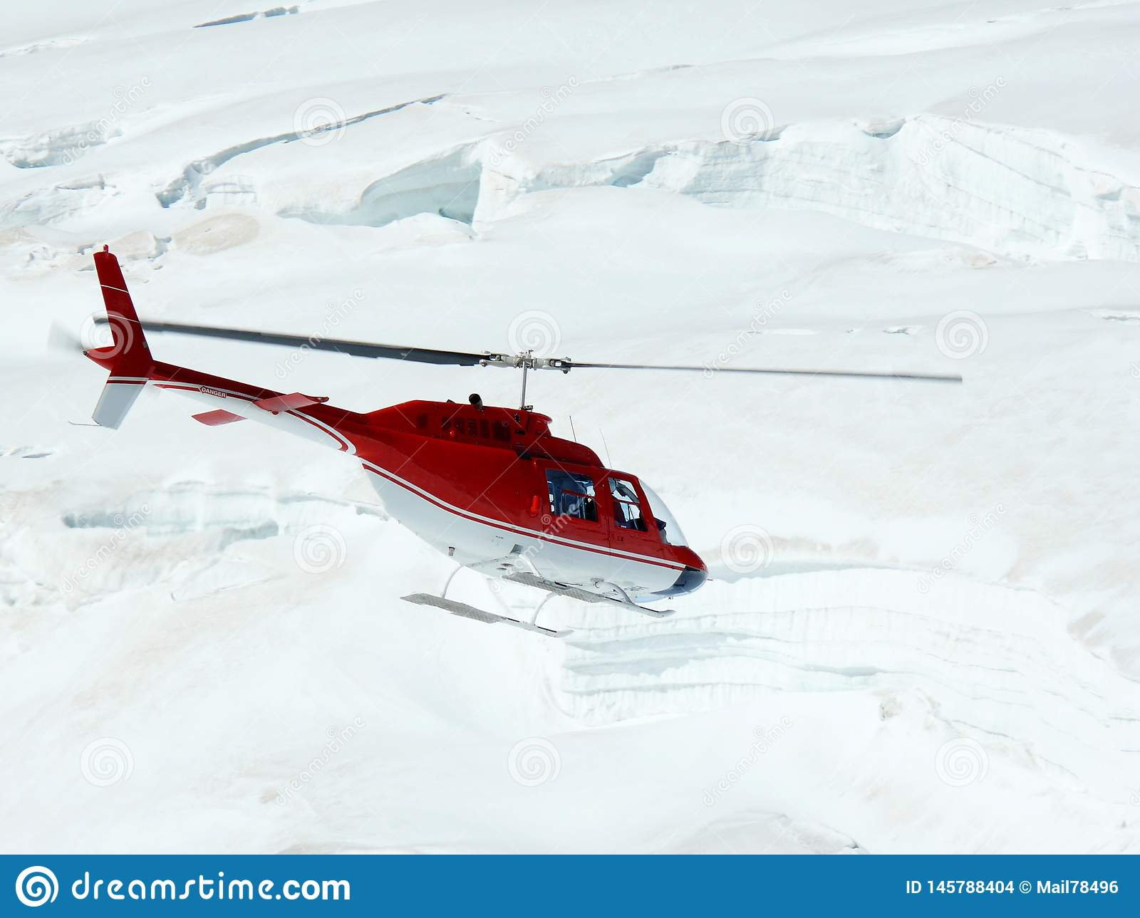 Jungfrau, Switzerlan.  Red helicopter on high mountain snow
