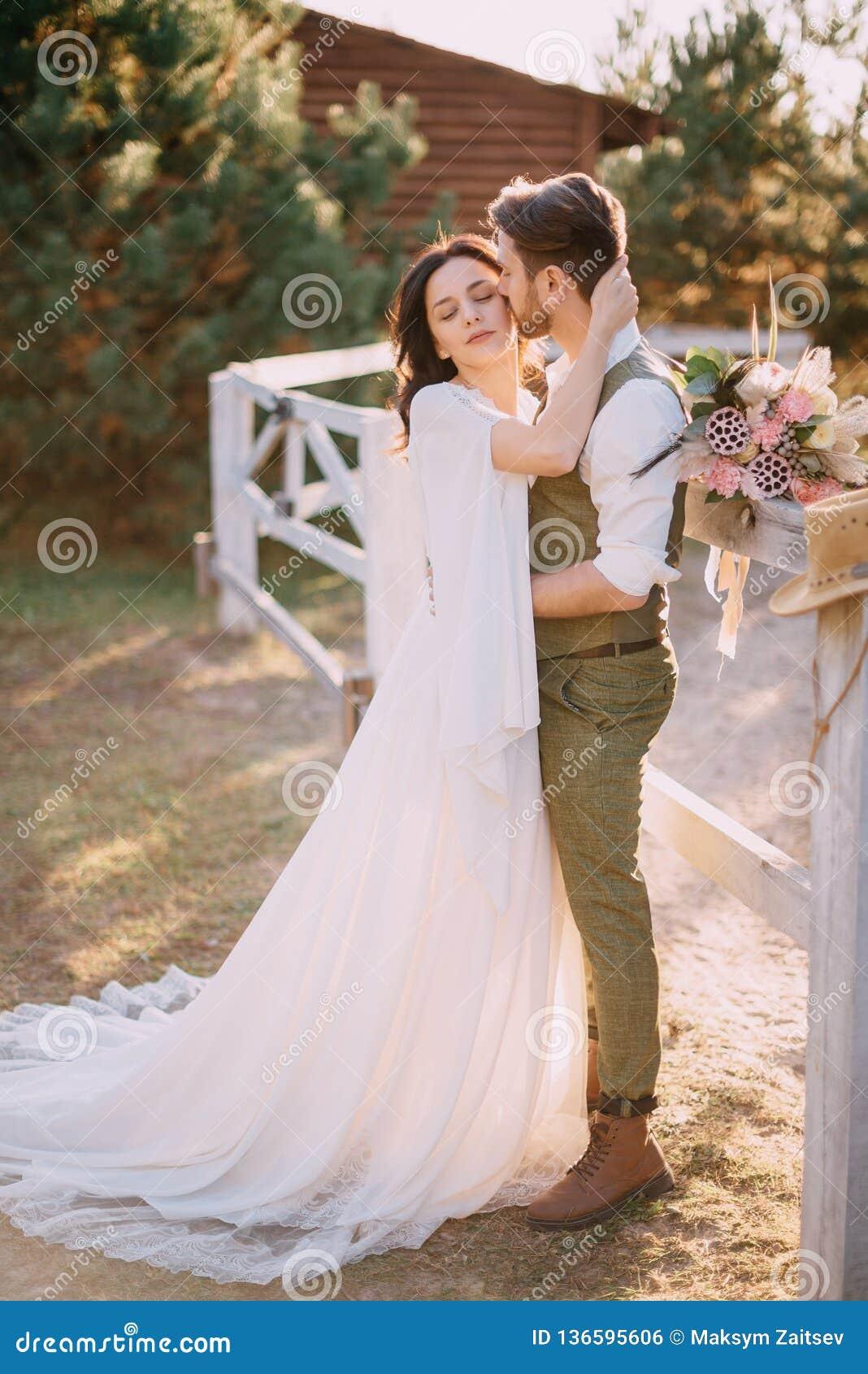 Jungvermählten in der Cowboyart, die auf Ranch steht und umarmt