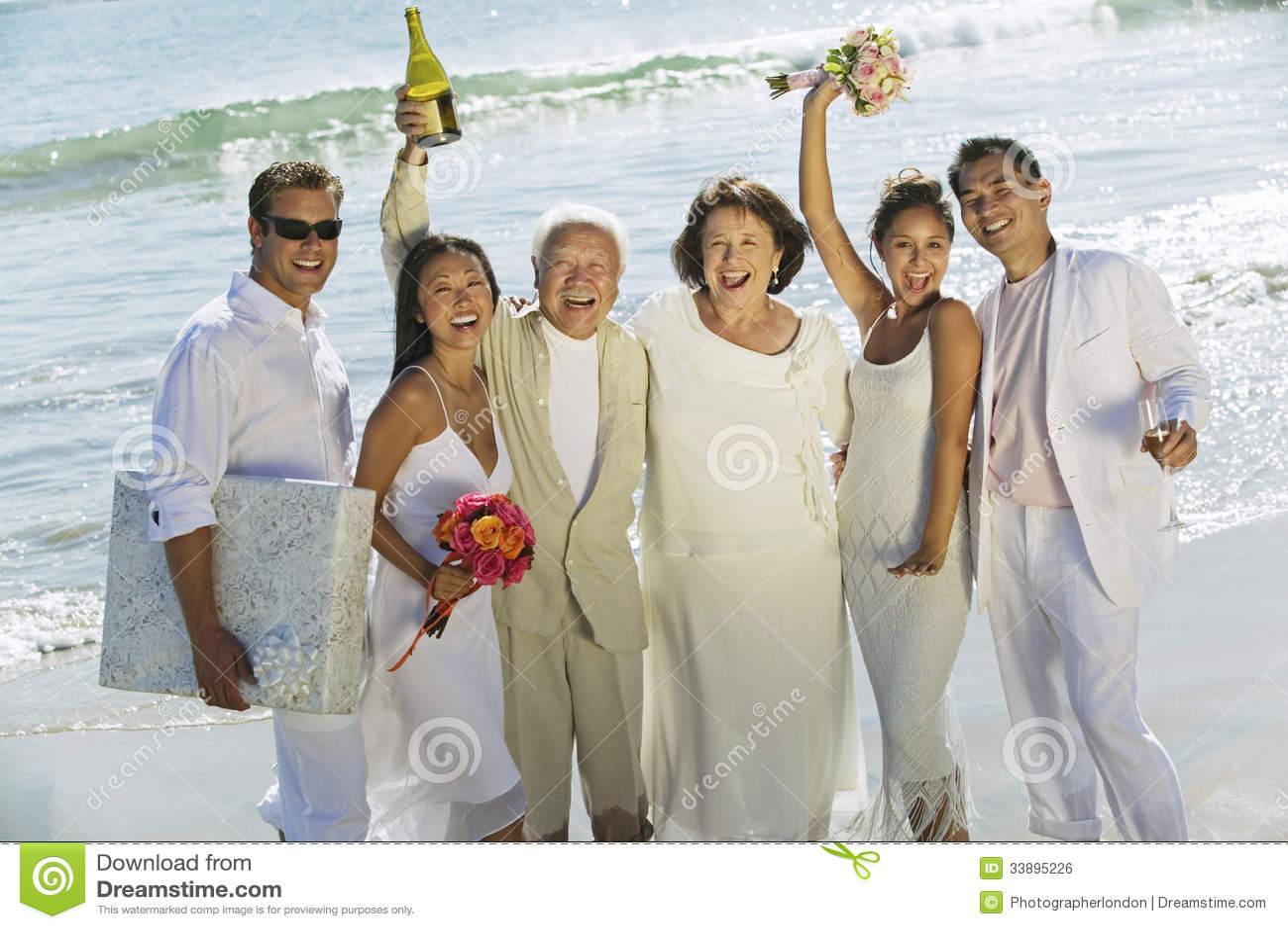 Jungvermählten-Paare mit der Familie, die auf Strand feiert