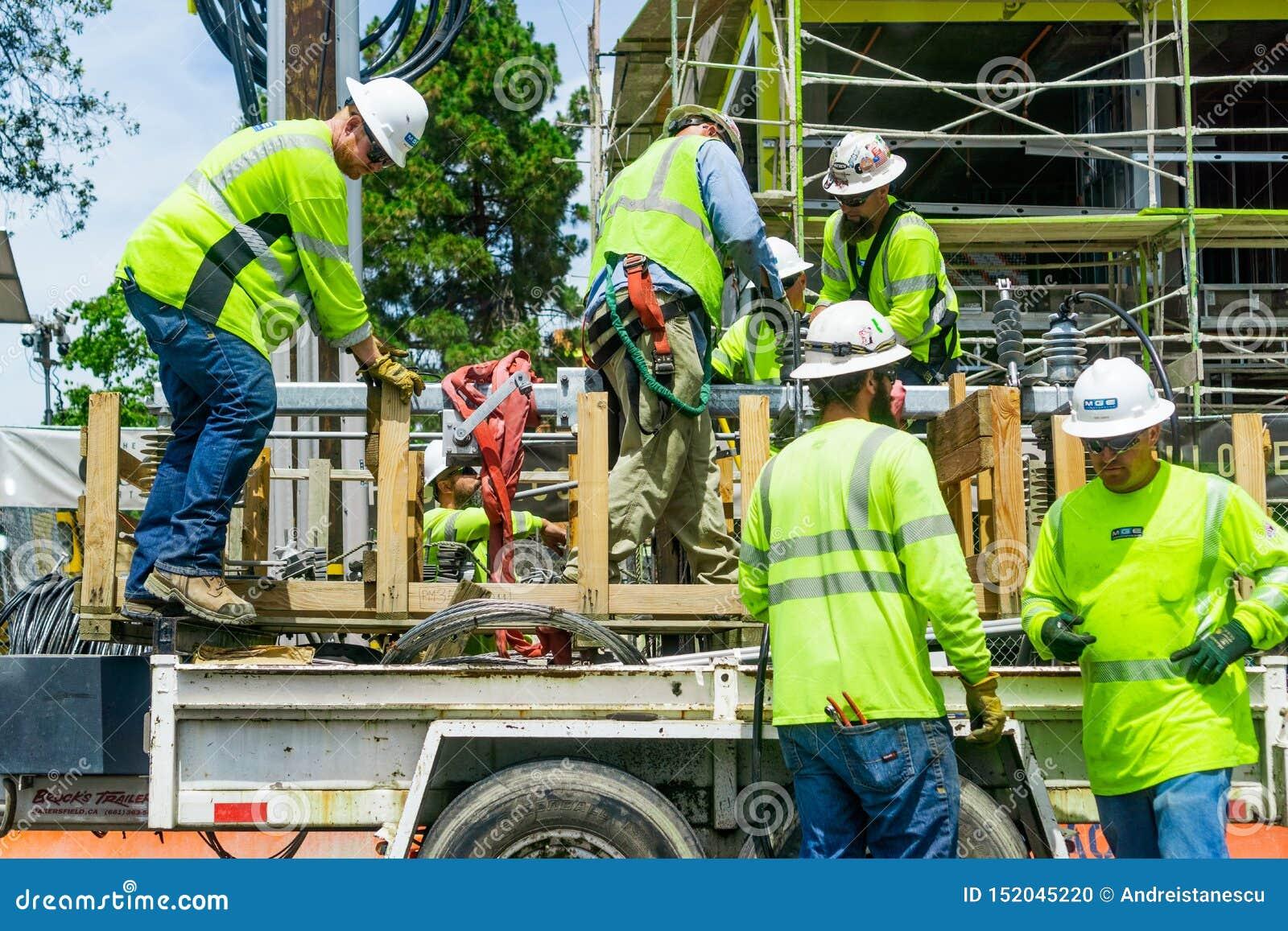 Juni 24, 2019 Mountain View/CA/de V.S. - Team van bouwvakkers die heldere gele vesten en bouwvakkers dragen