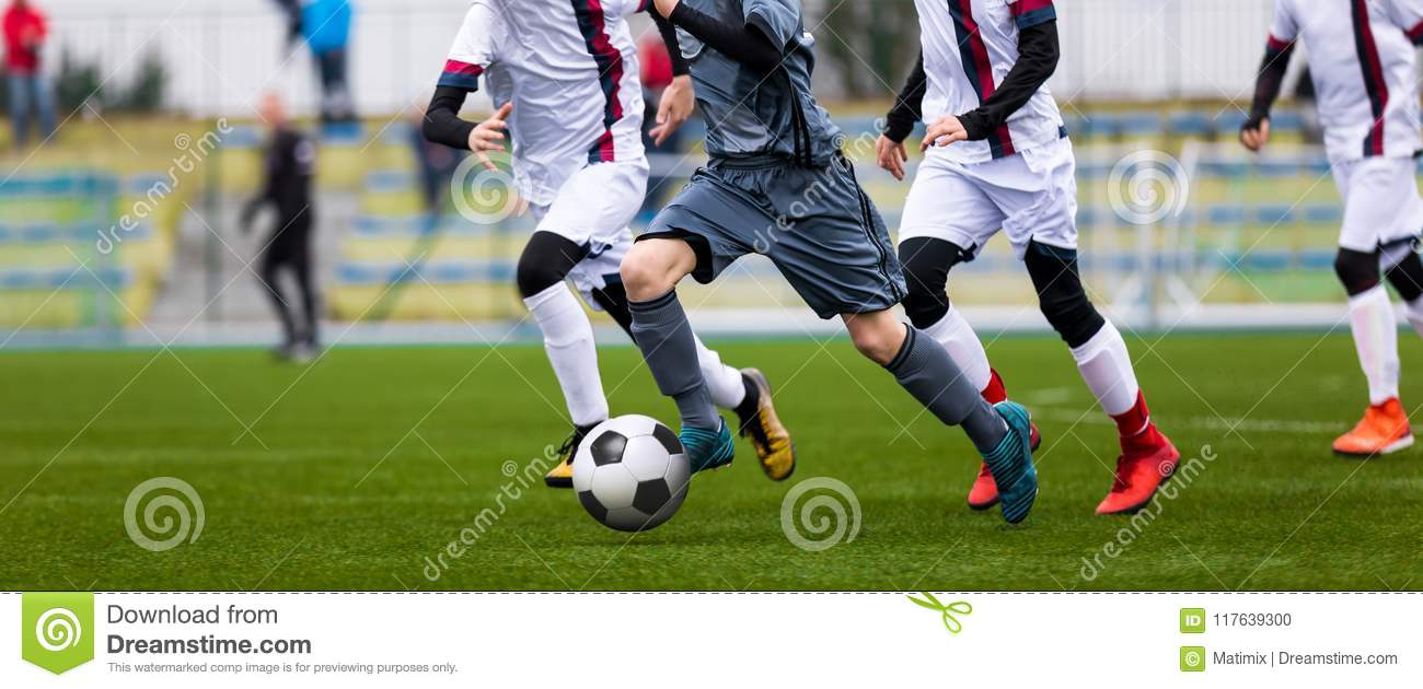 Junior Football Match. Soccer Game For Youth Players. Boys Playing Soccer Match on Football Pitch