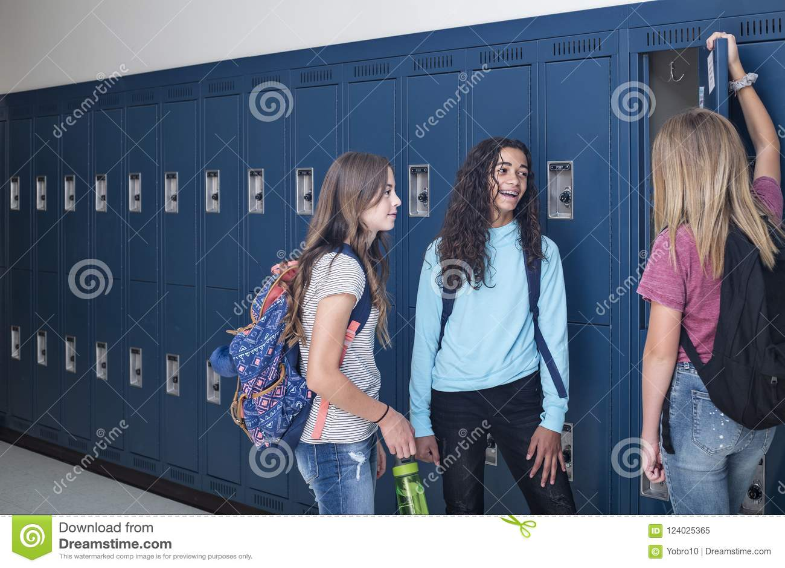 Junior High skolastudenter som talar och står vid deras skåp i ett skolahall