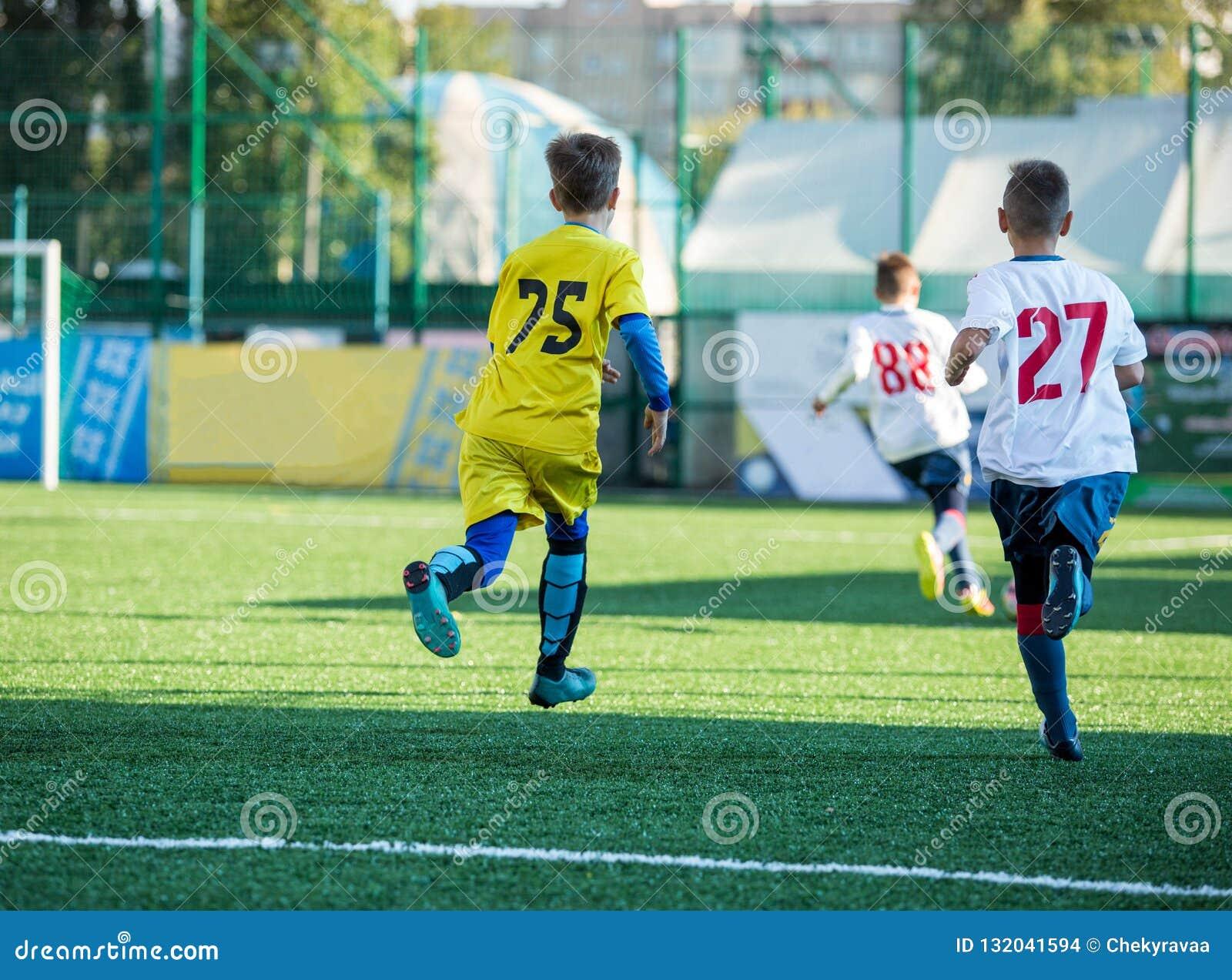 Juniorfußballspiel Fußball-Spiel für Jugend-Spieler Jungen in der gelben und weißen Uniform, die Fußballspiel spielt Fußballstadi