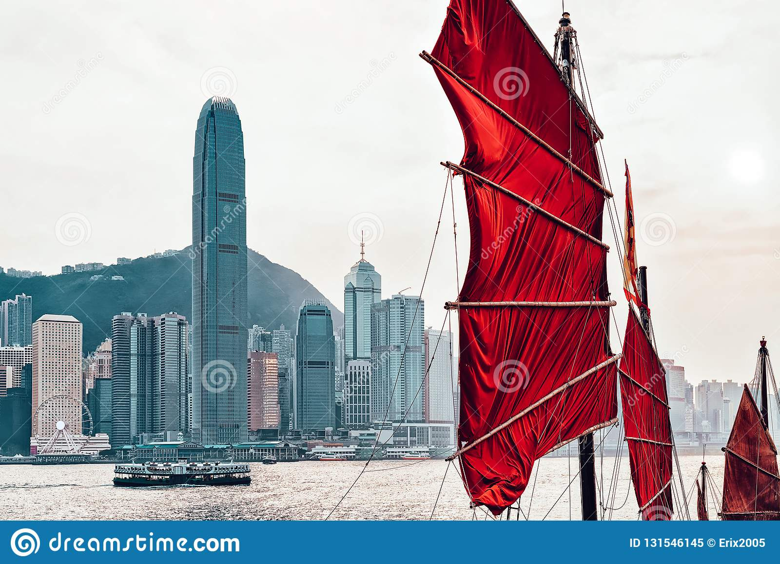 Junk boat in Victoria Harbor in HK at sunset. View from Kowloon on Hong Kong Island royalty free stock photo