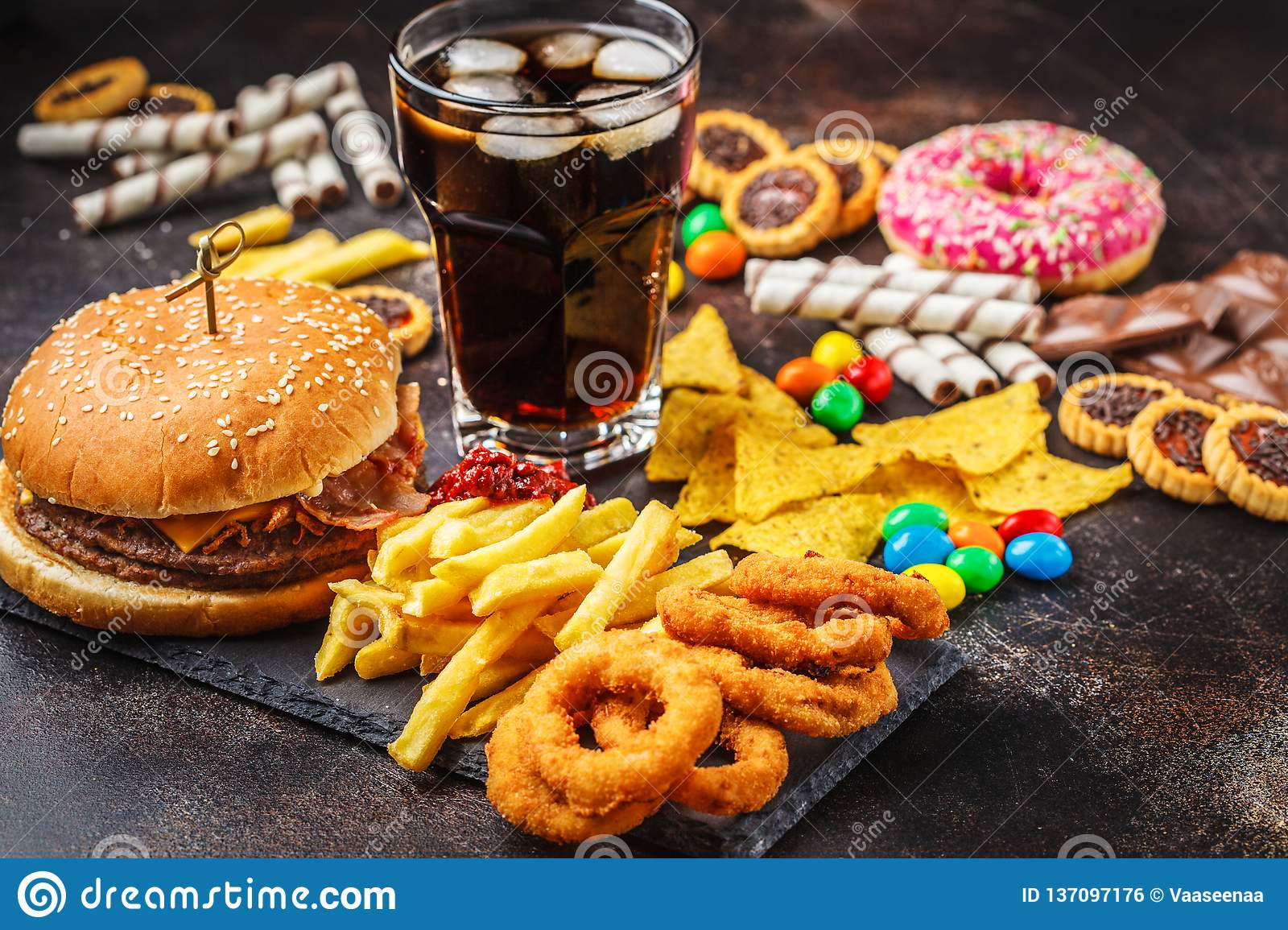 Junk food concept. Unhealthy food background. Fast food and sugar. Burger, sweets, chips, chocolate, donuts, soda