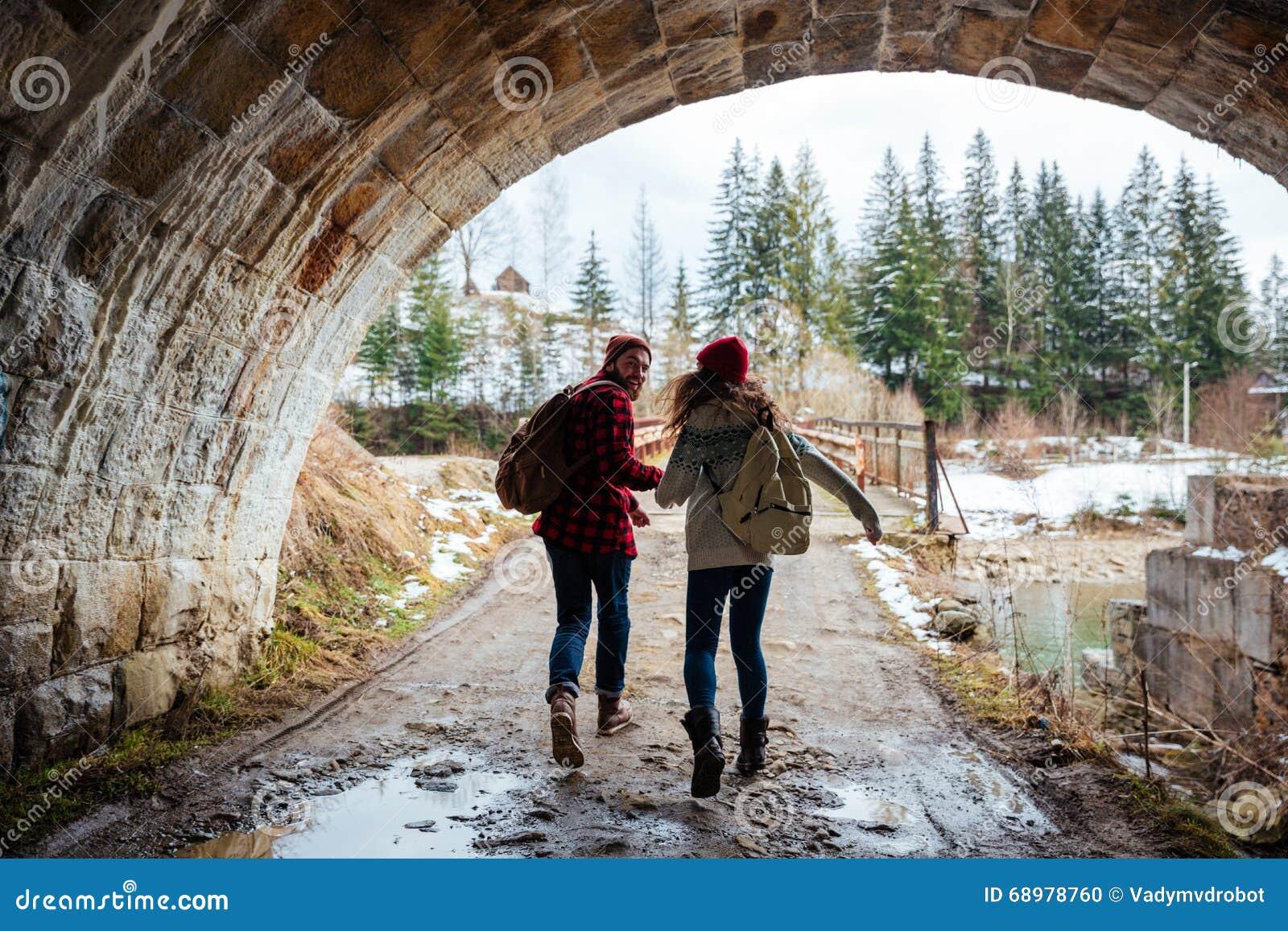 Junte celebrar las manos y el funcionamiento junto debajo del puente
