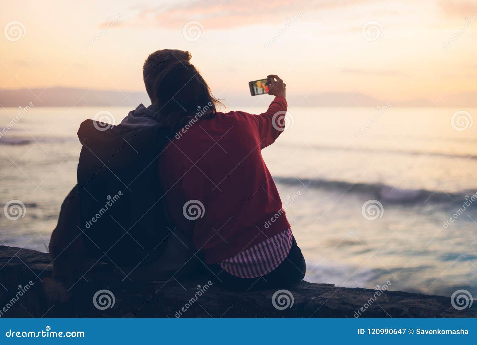 Junte el abrazo en salida del sol del océano de la playa del fondo, tome las fotos en el smartphone móvil, dos personas romántica