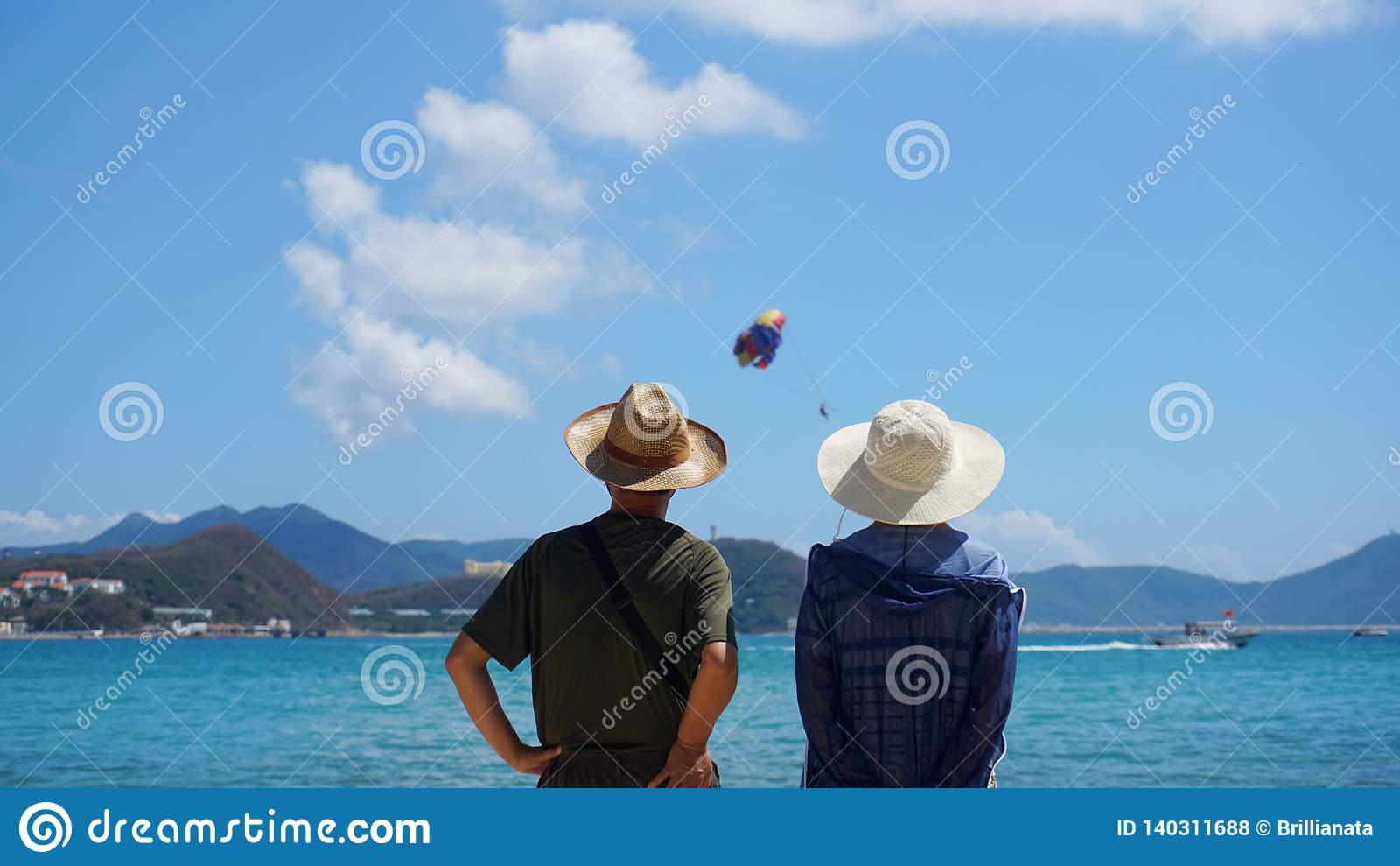 Junte el hombre y a la mujer que permanecen en la playa de la playa
