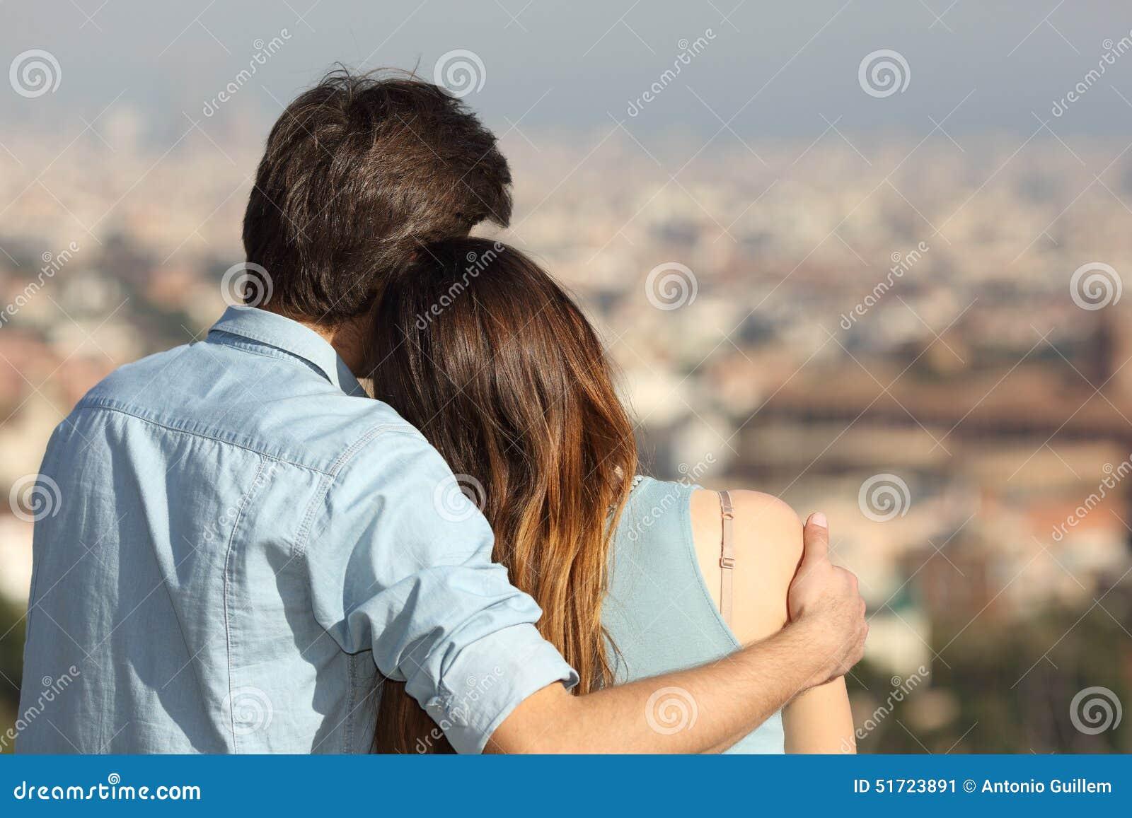 Junte la datación en amor y el abrazo mirando la ciudad