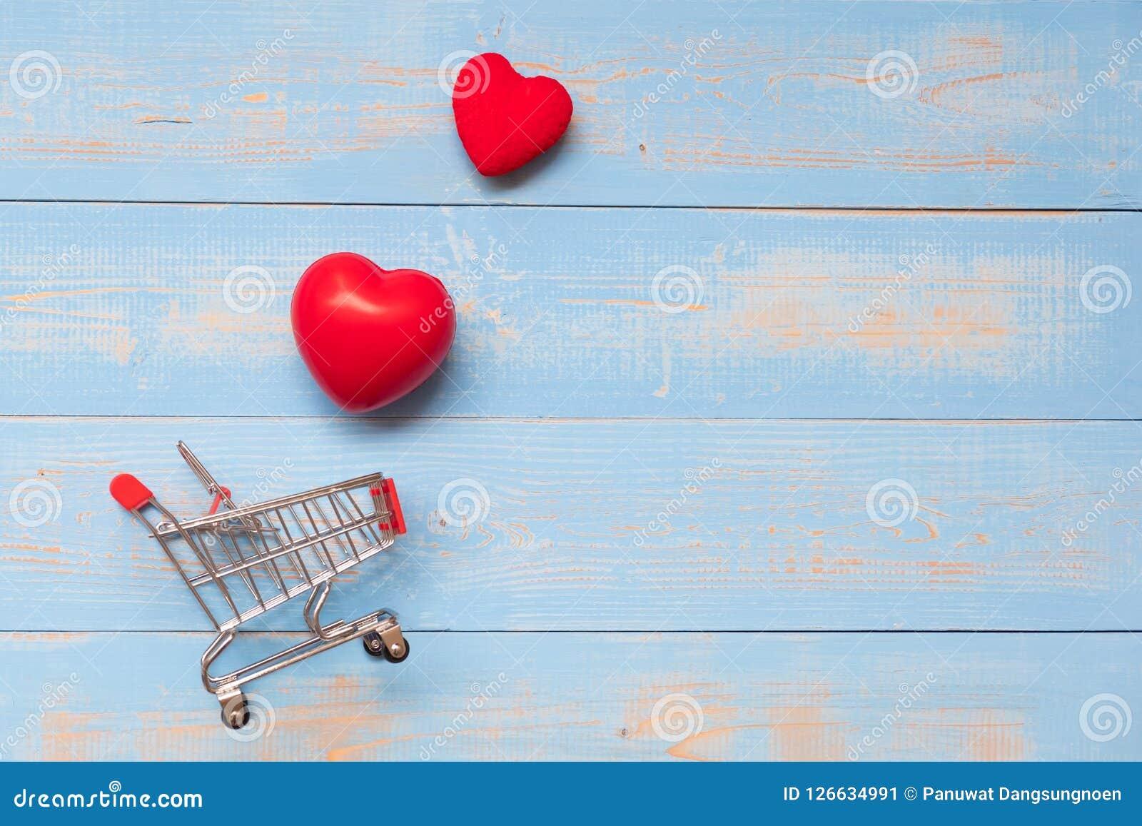 Junte la forma roja del corazón con el mini carro de la compra en la tabla de madera en colores pastel azul amor, compras y Valen