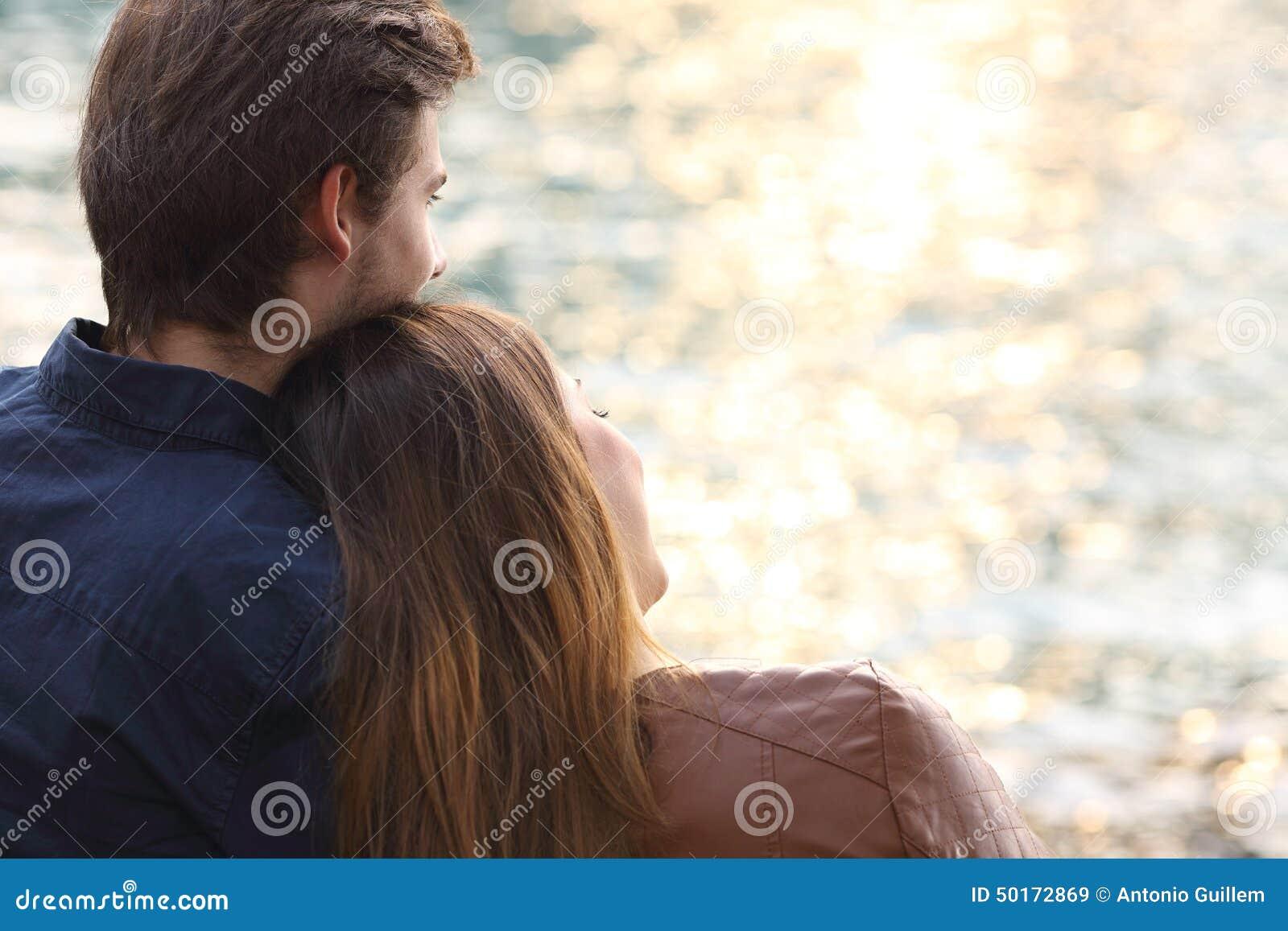 Junte la puesta del sol de abrazo y de observación en la playa