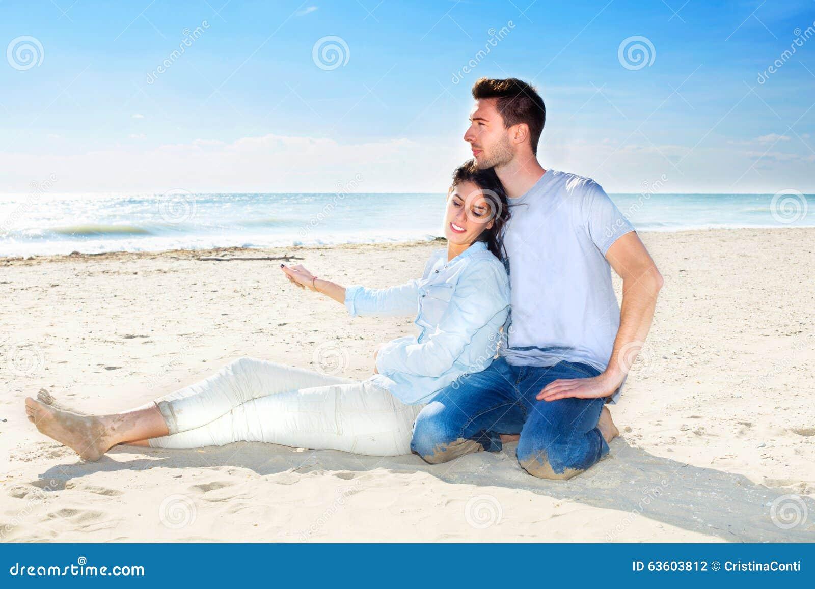 Junte la relajación en la arena en la playa que mira el mar