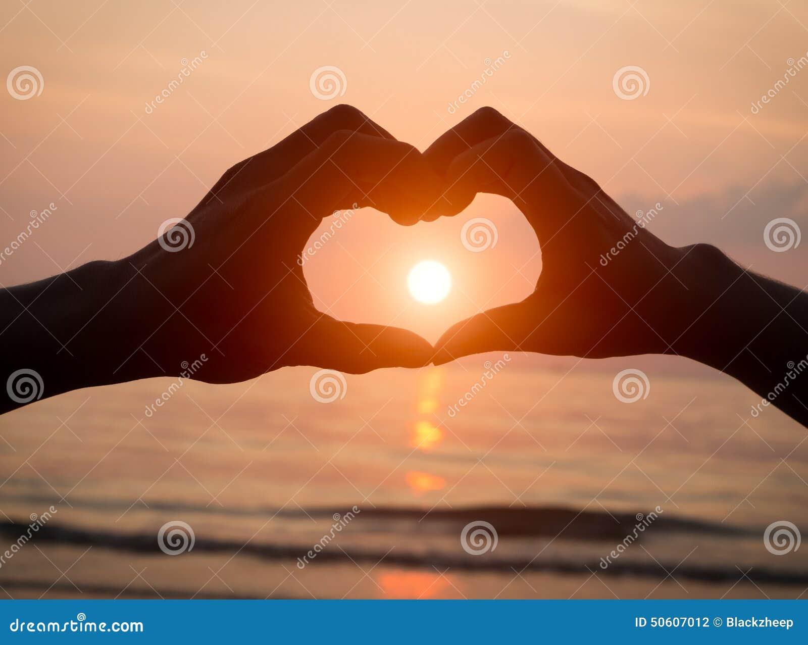 Junte llevar a cabo amor del corazón de las manos en la puesta del sol en la playa