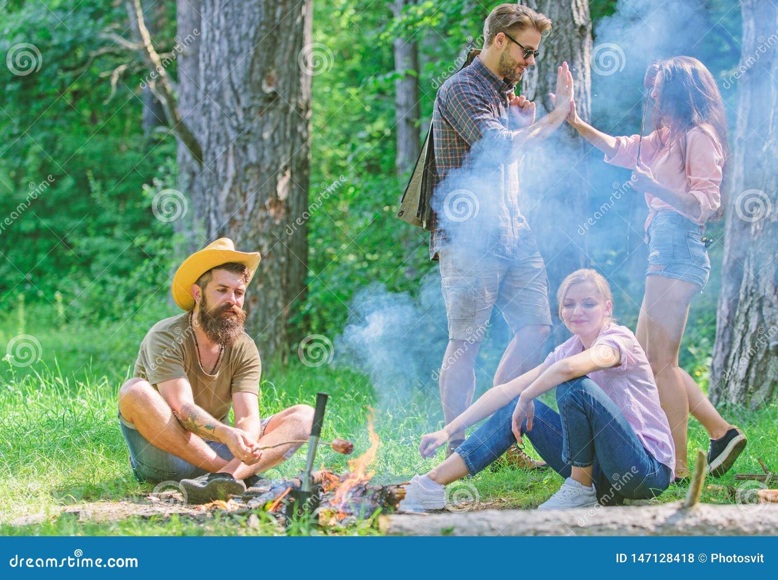 Junte-se ao piquenique do ver?o Os amigos que encontram-se perto da fogueira para pendurar para fora e preparar-se roasted o fund