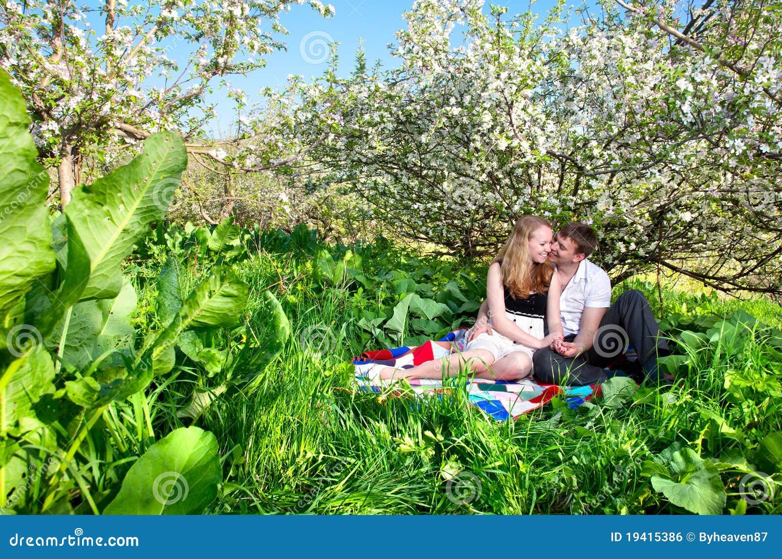 Junte sentarse bajo árbol florido