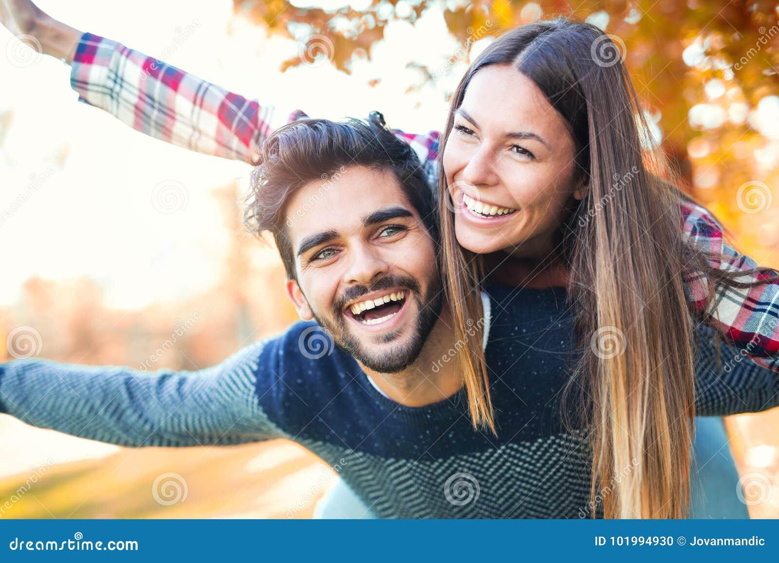 Junte tener el hombre de la diversión que da a cuestas a la mujer en parque