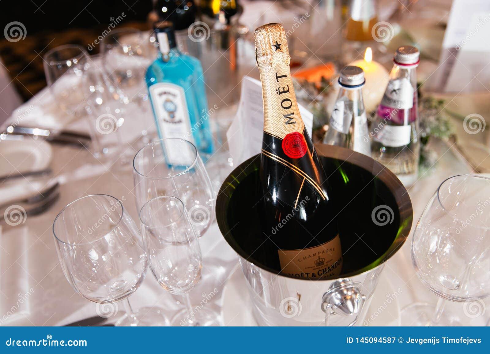 JURMALA, LETLAND - JANUARI 01, 2019: De champagne van de Moetluxe op een lijst met een fles jenever Bombay op de achtergrond