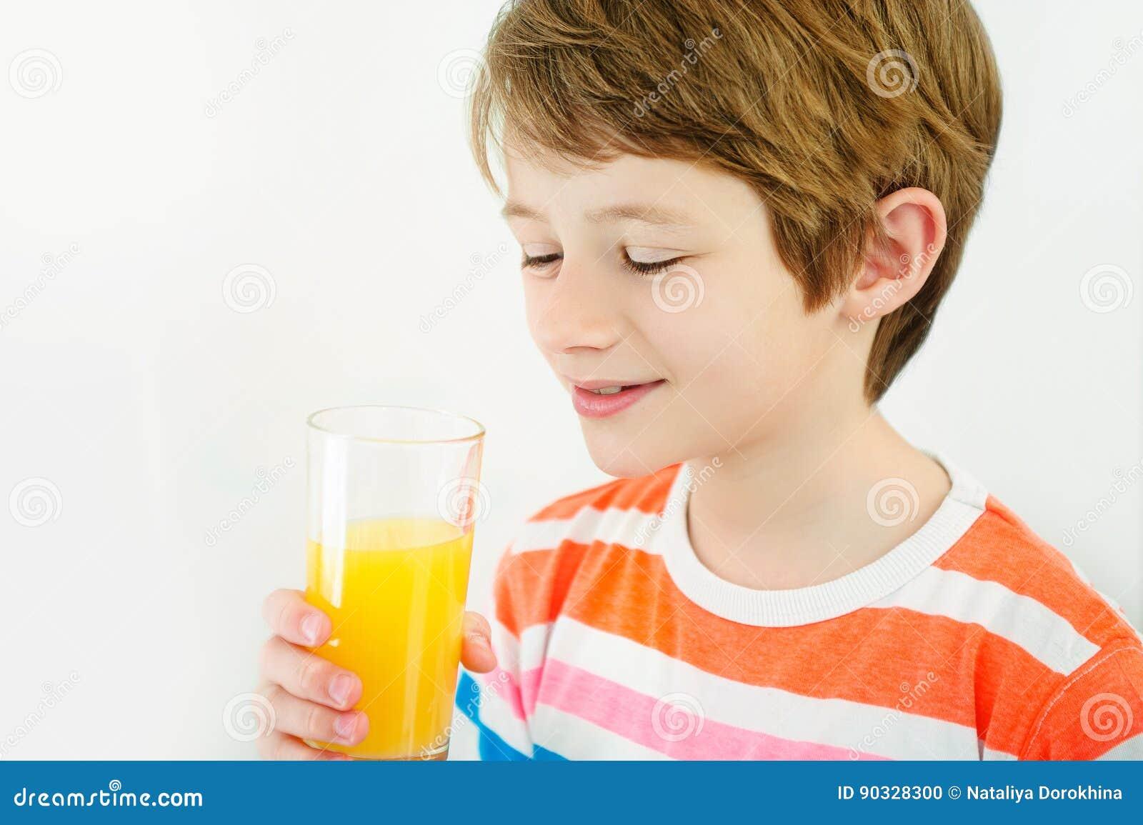 Jus d orange de boissons de garçon avec une paille