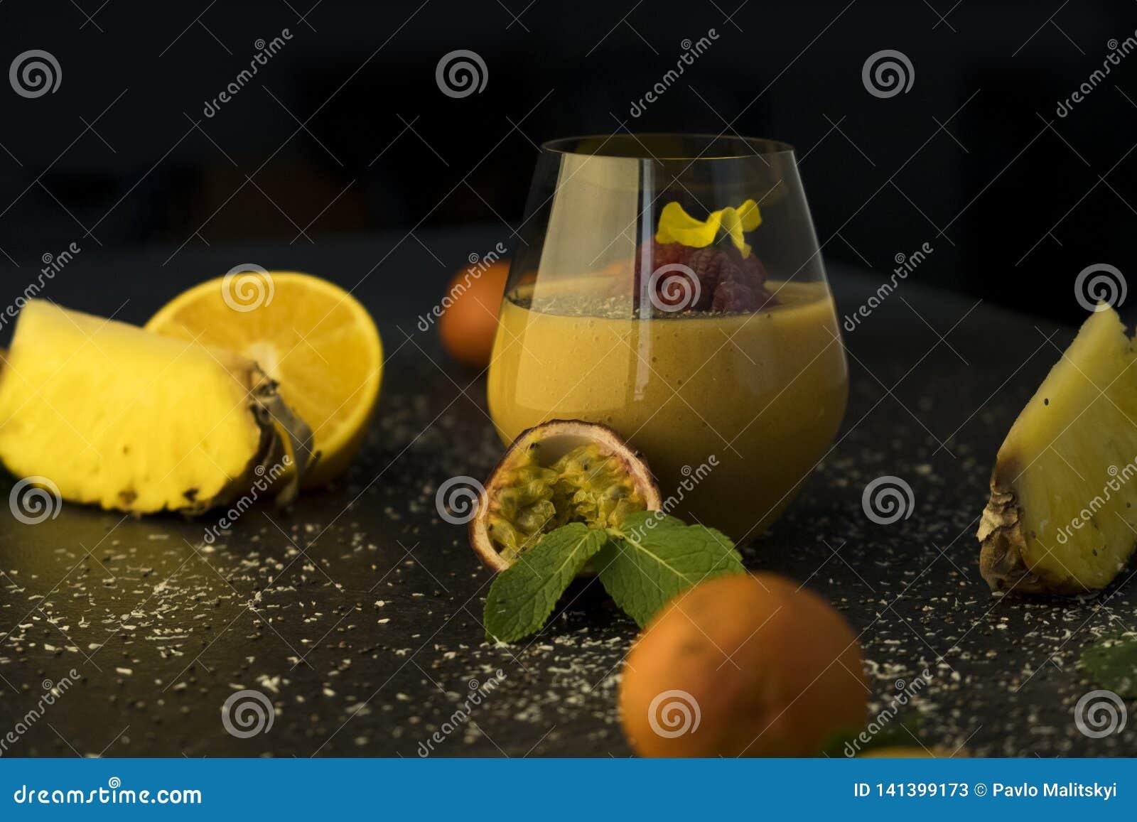 Jus de smoothie de macédoine de fruits dans un verre transparent sur la table, les oranges et les mandarines avec l ananas et pas