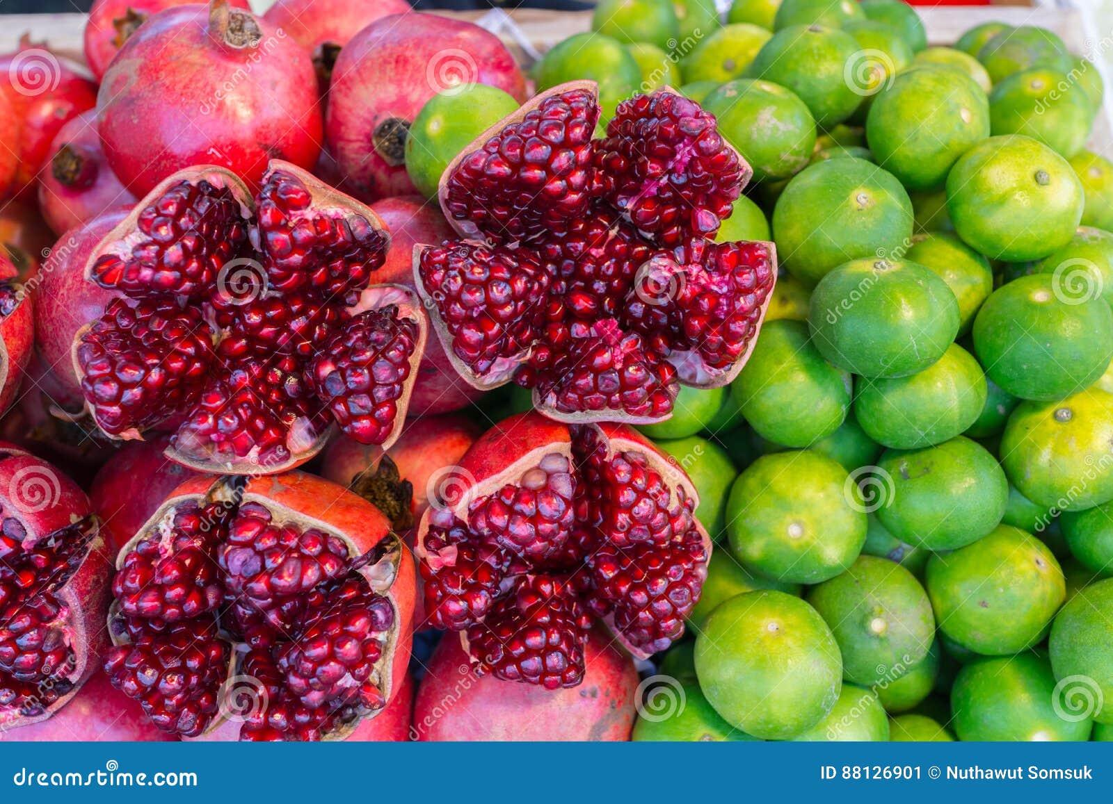 Jus frais de grenade rouge colorée et de citron vert de tropique