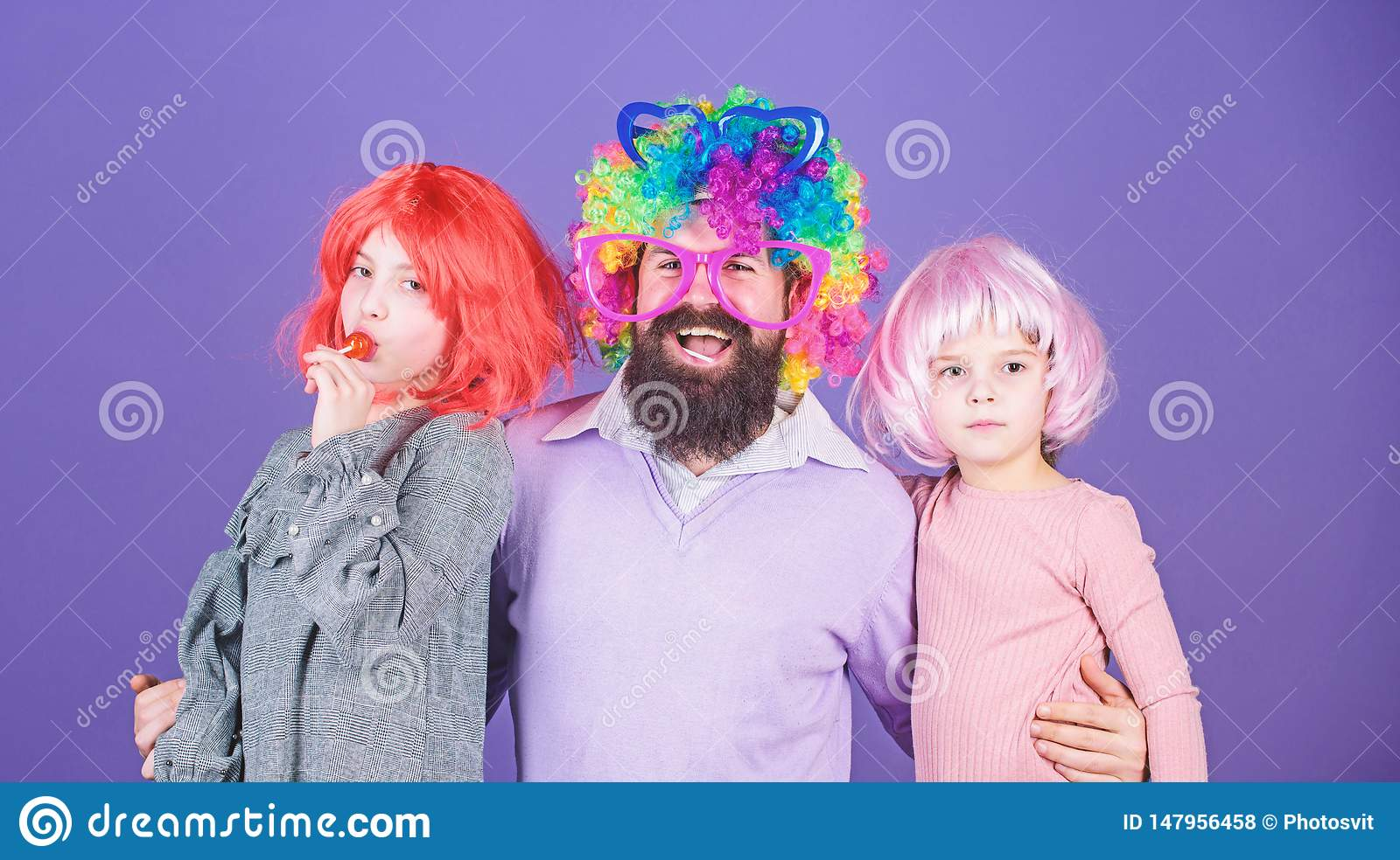 Just for fun. Party time. How crazy is your father. Man bearded father and kids girls wear colorful wig violet