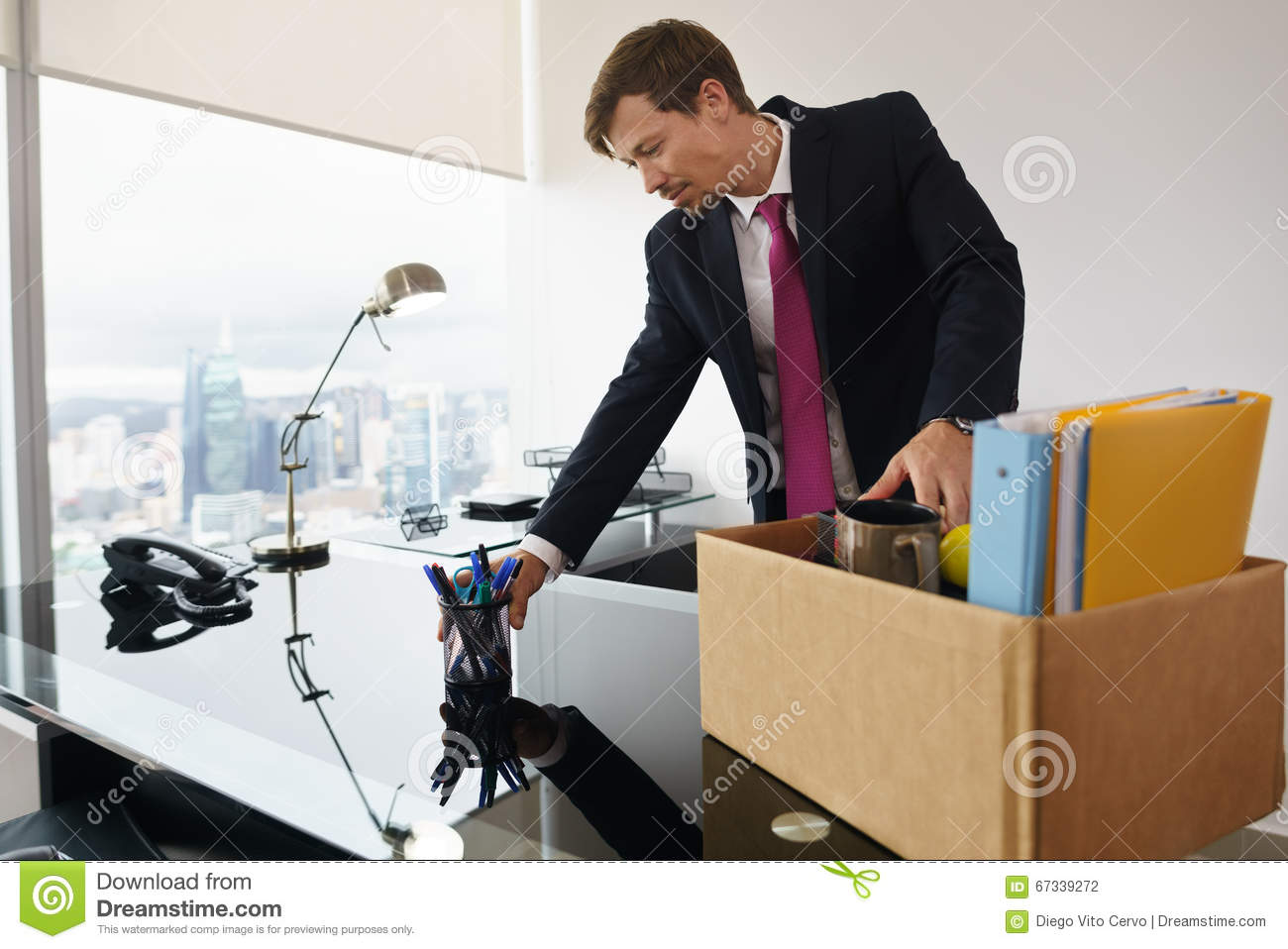 just hired business man in new office putting desk in. Black Bedroom Furniture Sets. Home Design Ideas