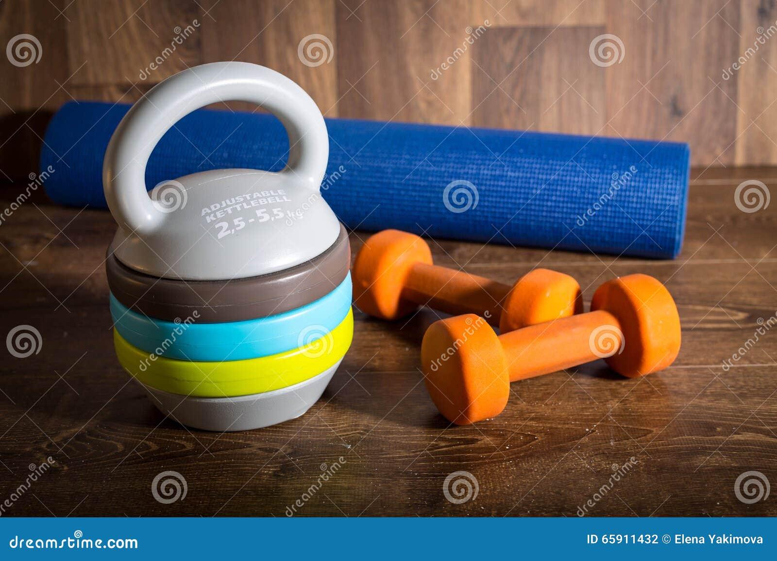 Justerbar kettlebell, par av orange hantlar och yoga som är matt på träbakgrund Vikter för en konditionutbildning