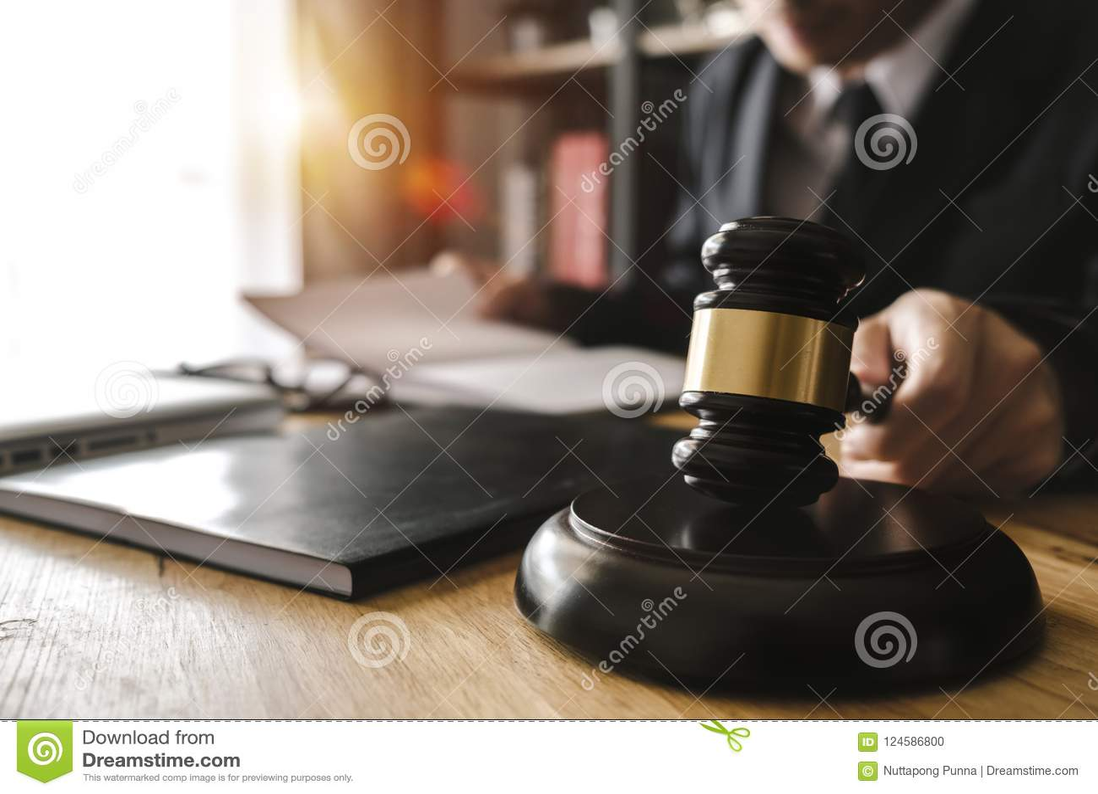 Justiça e conceito da lei Juiz masculino em uma sala do tribunal com o martelo, trabalhando com, tabuleta digital
