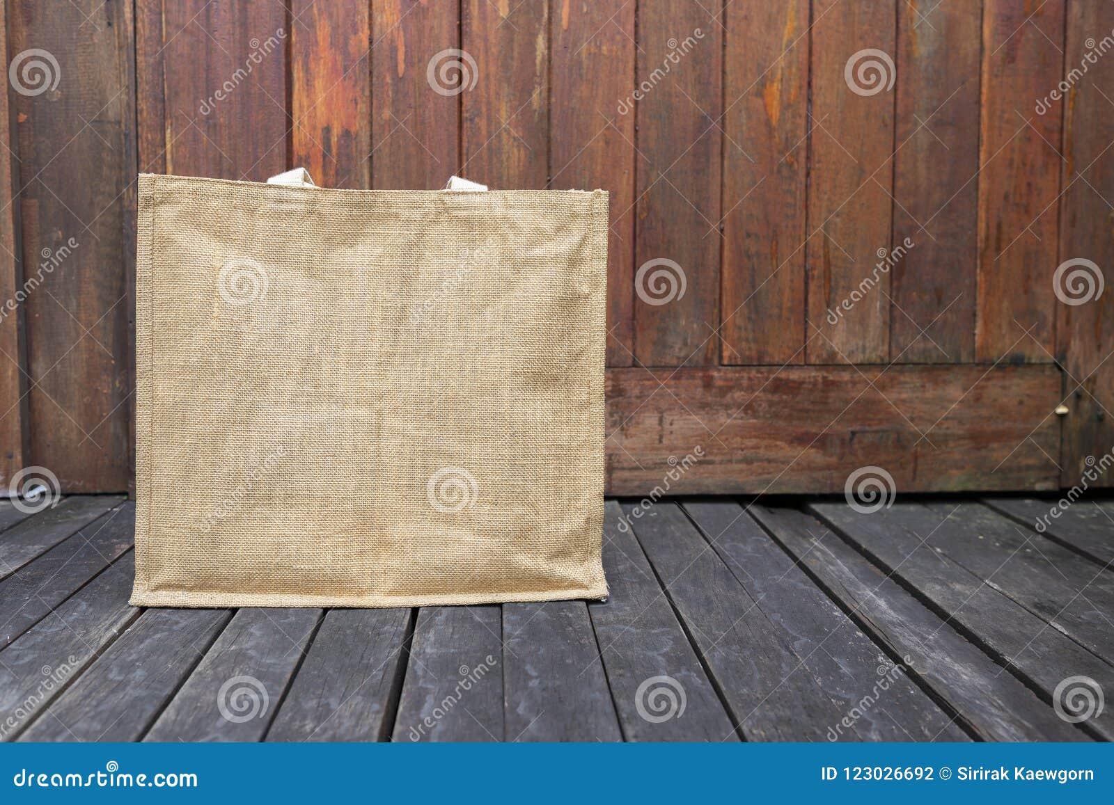 Jutowa torba na drewnianej podłoga z przestrzenią na drewnianym tle