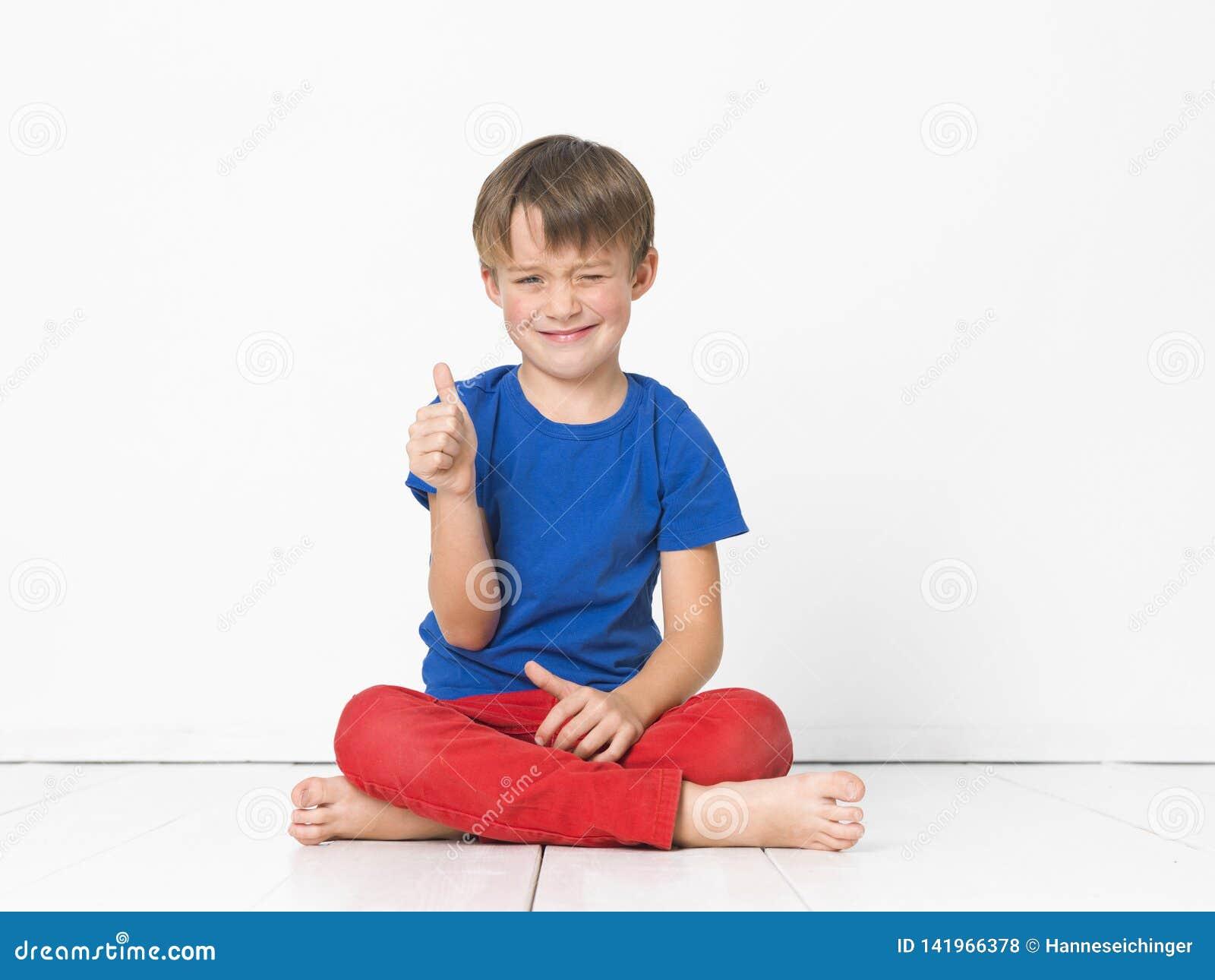 Kühler und netter und schöner sechs Jährigjunge mit roter Hose und blauem Hemd auf weißem Boden