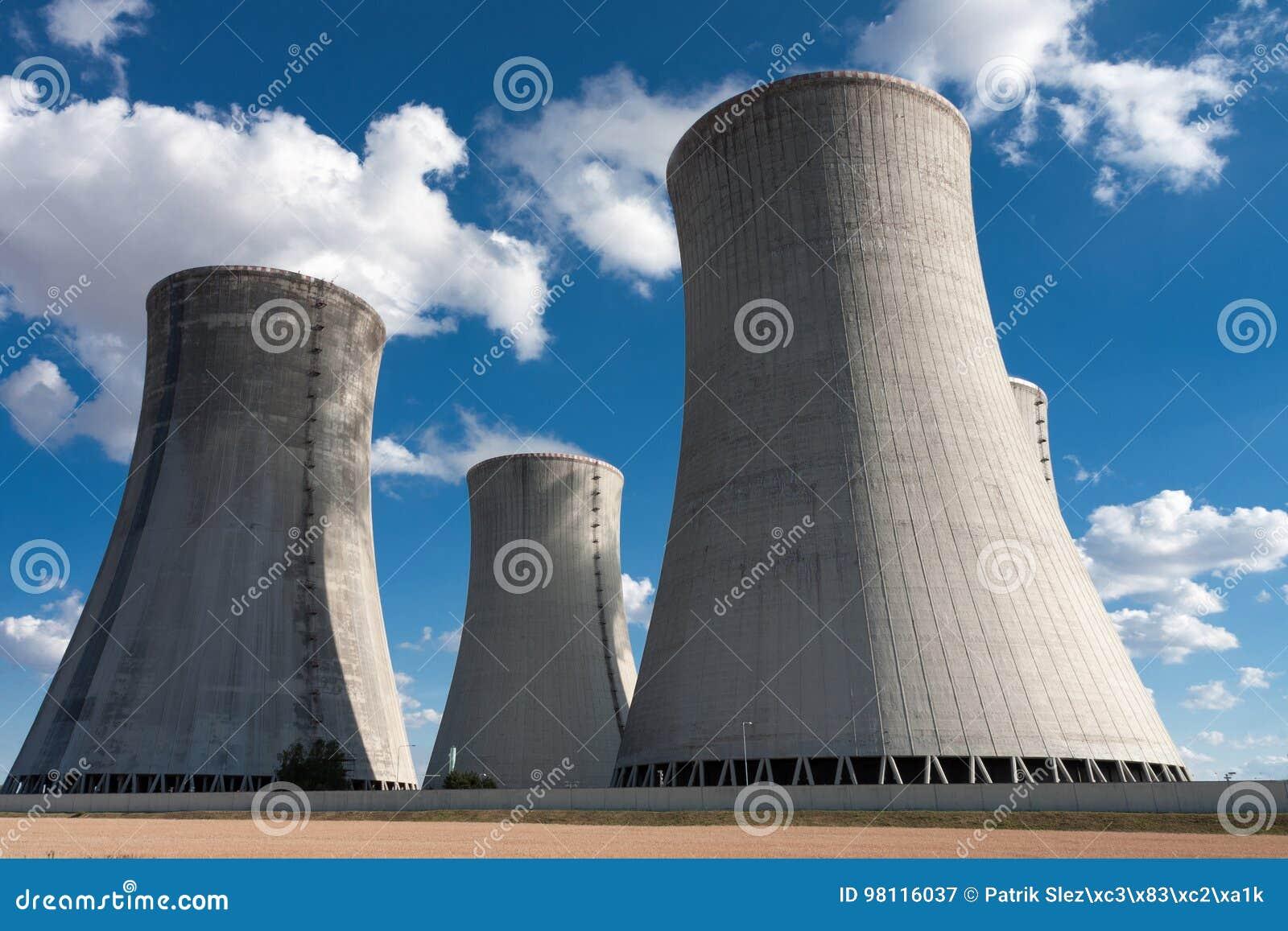 Kärnkraftverket som kyler står högt mot blå himmel
