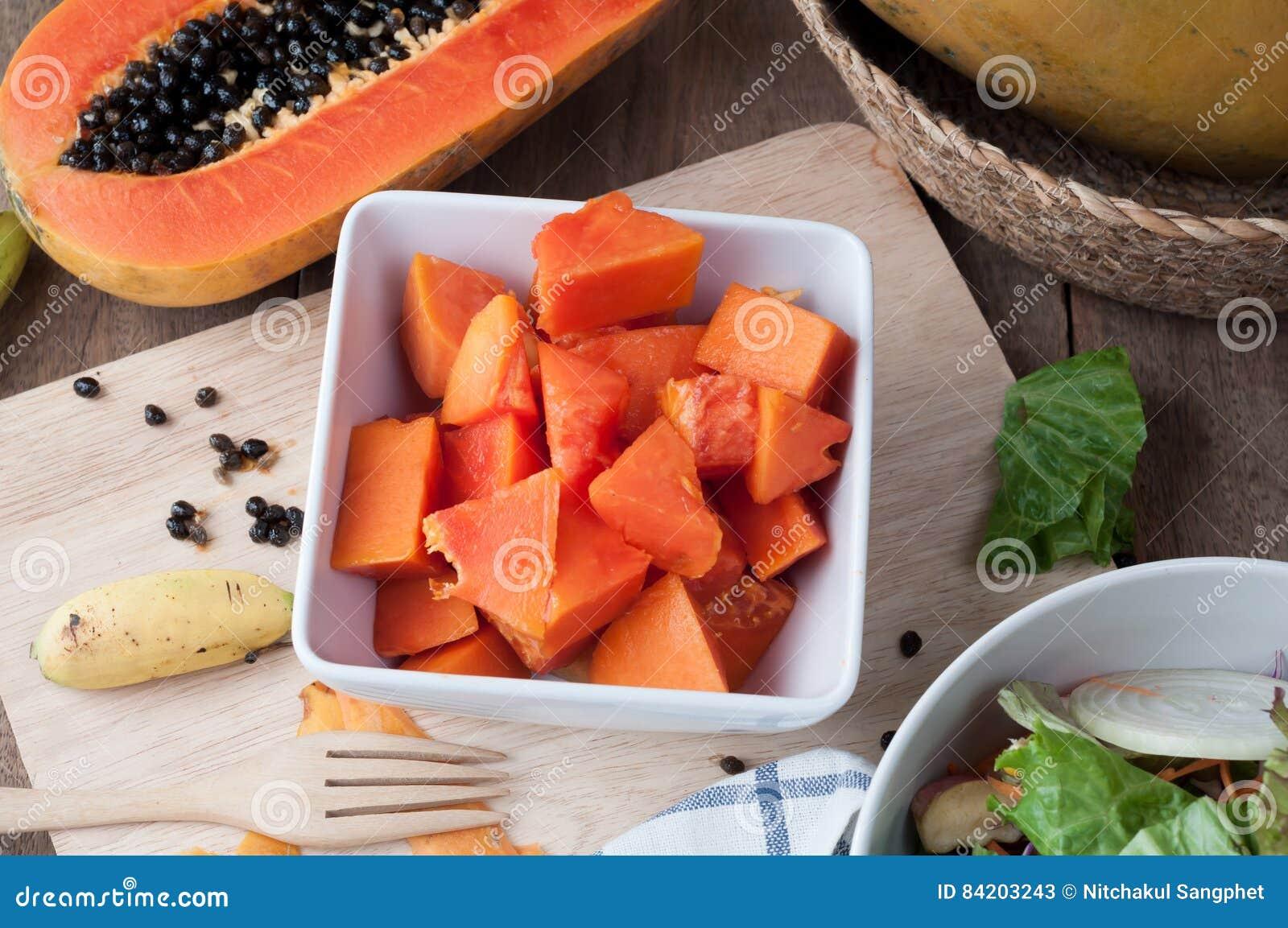 Köksbord med skivad ny papayafrukt på den wood bitande boaen