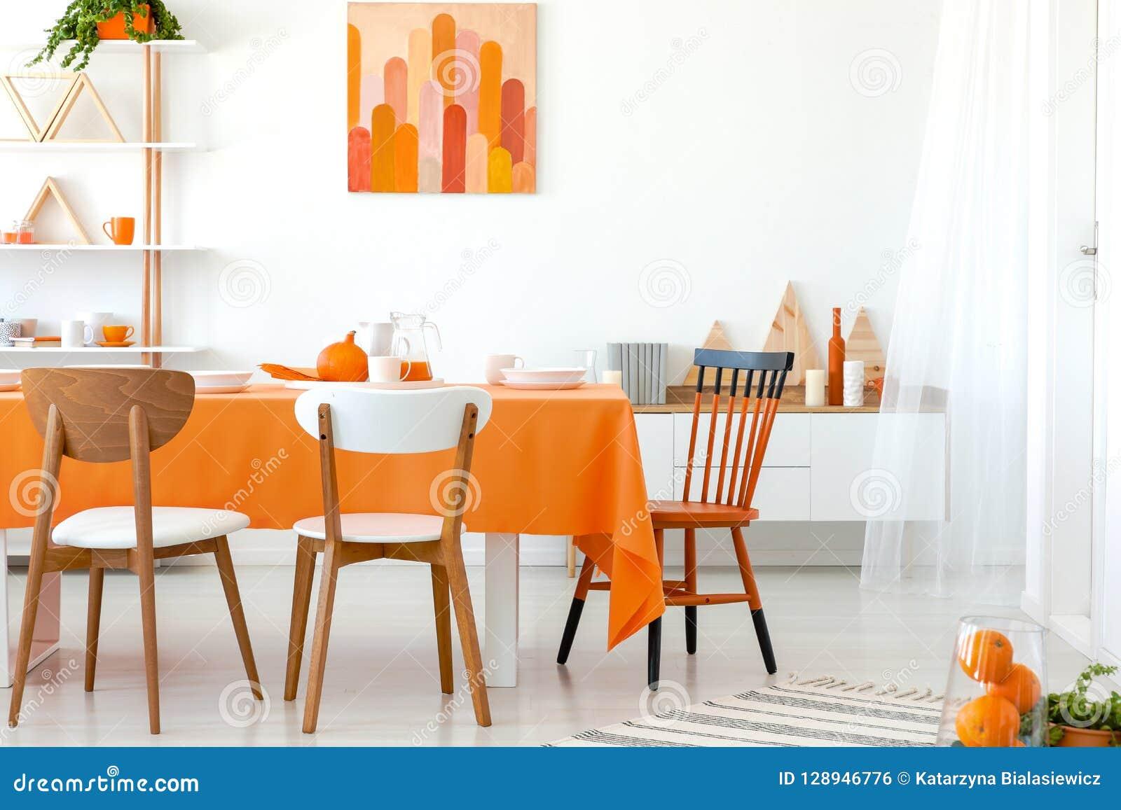 Köksbord som täckas med den orange bordduken och vit disk Konstverk på väggen och hylla i hörnet