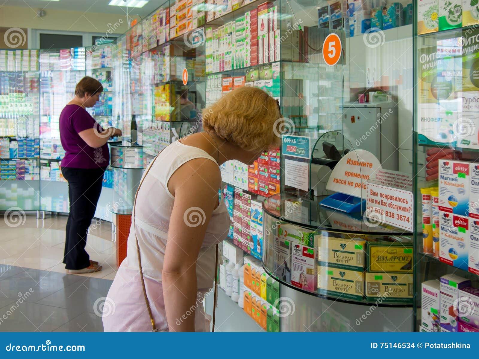 Köpare av verkligt folk som står på fönstret av apoteket av Alushta