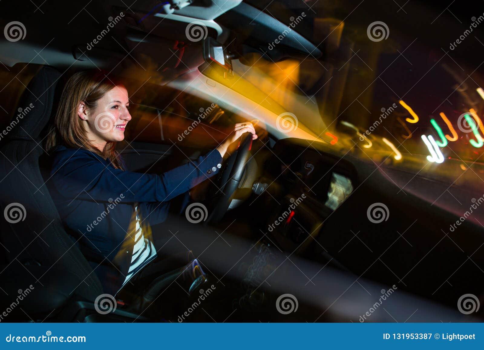 Köra en bil på den nätta natten -, ung kvinna som kör hennes bil