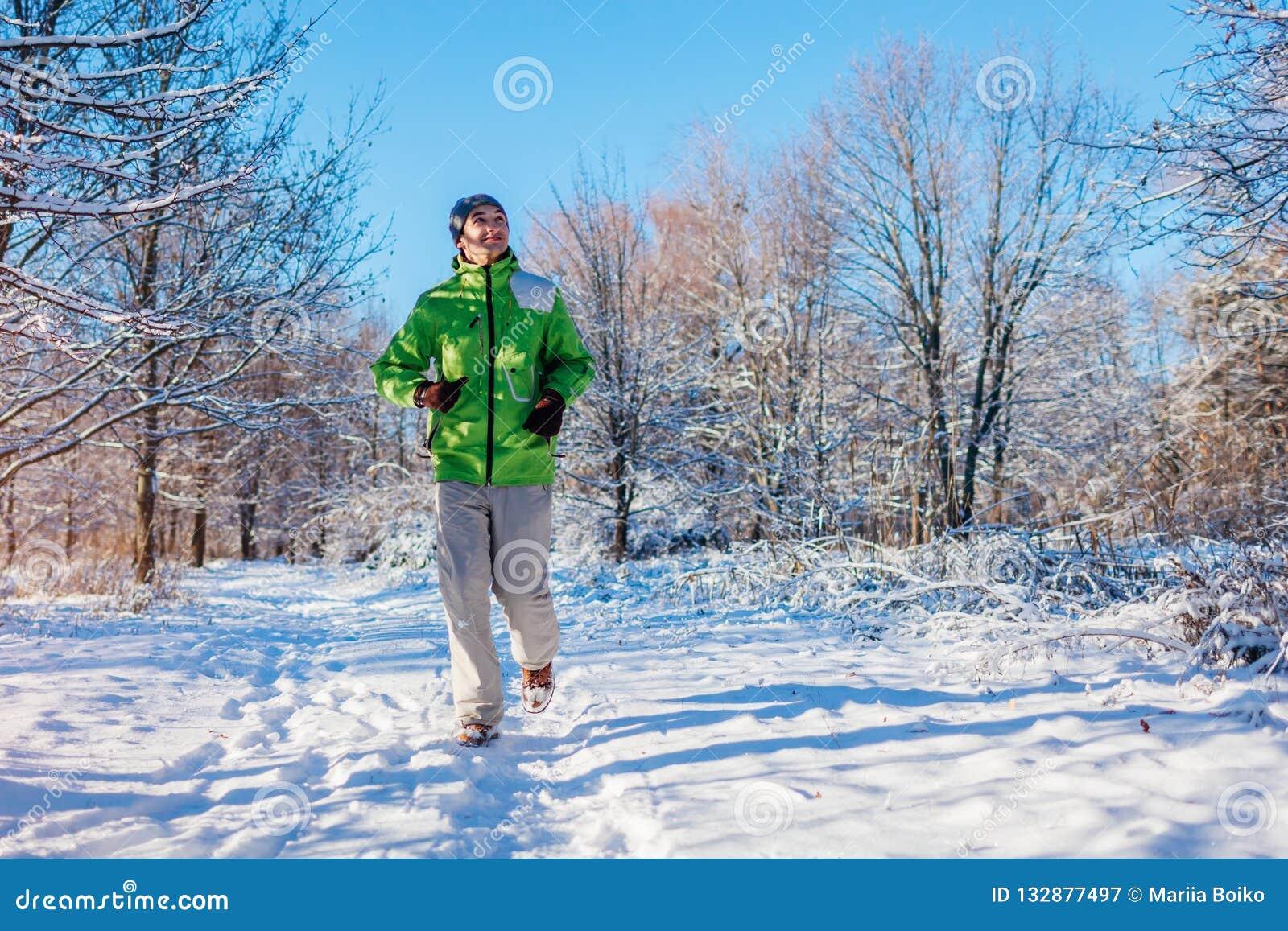 Körande idrottsman nenman som sprintar i yttersida för vinterskogutbildning i kallt snöig väder Aktiv sund livsföring