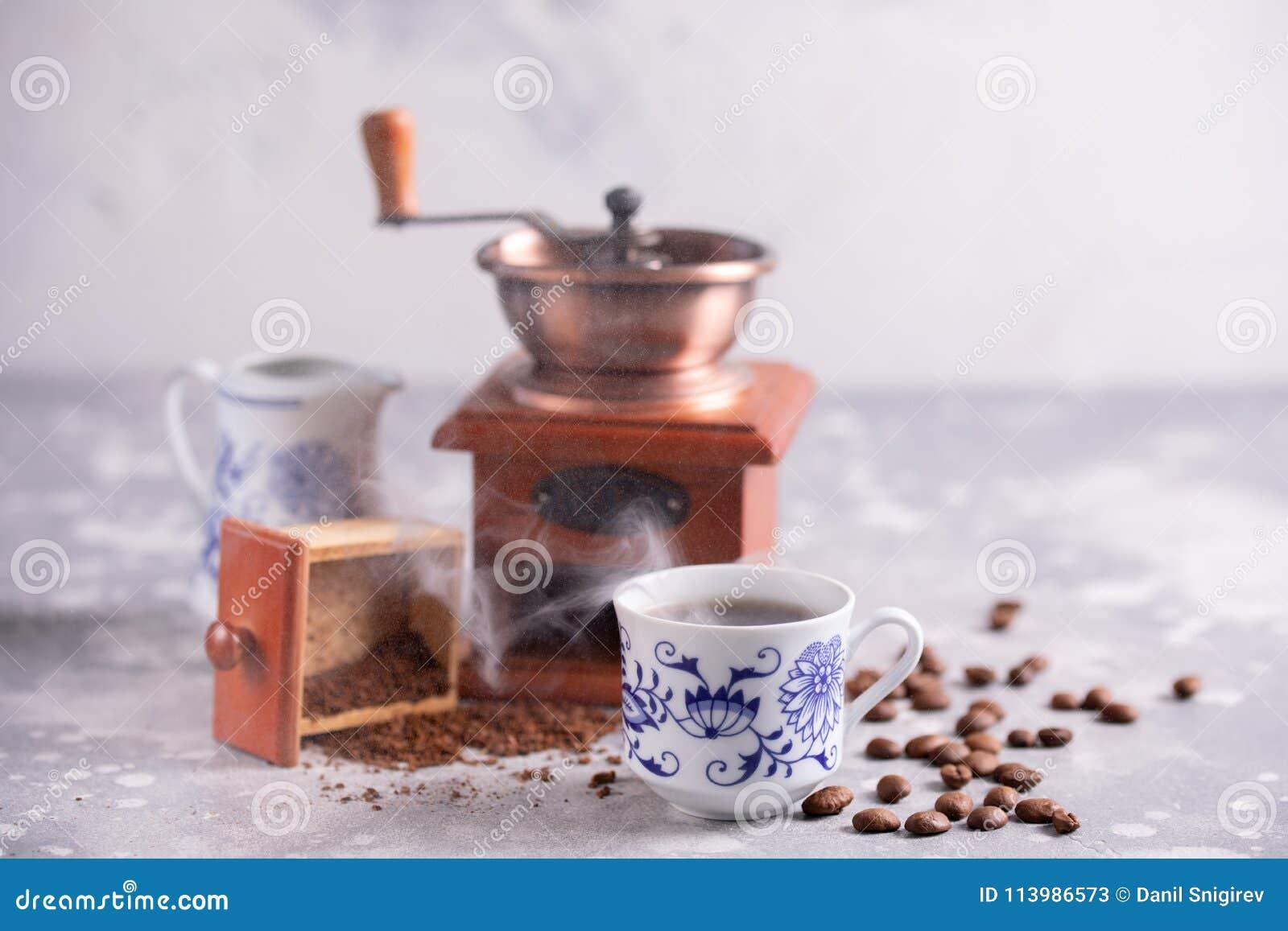 Körner des Kaffees fallen aus einer Weinlesekaffeemühle heraus Heißer schwarzer Kaffee in einem schönen Porzellan höhlen auf dem
