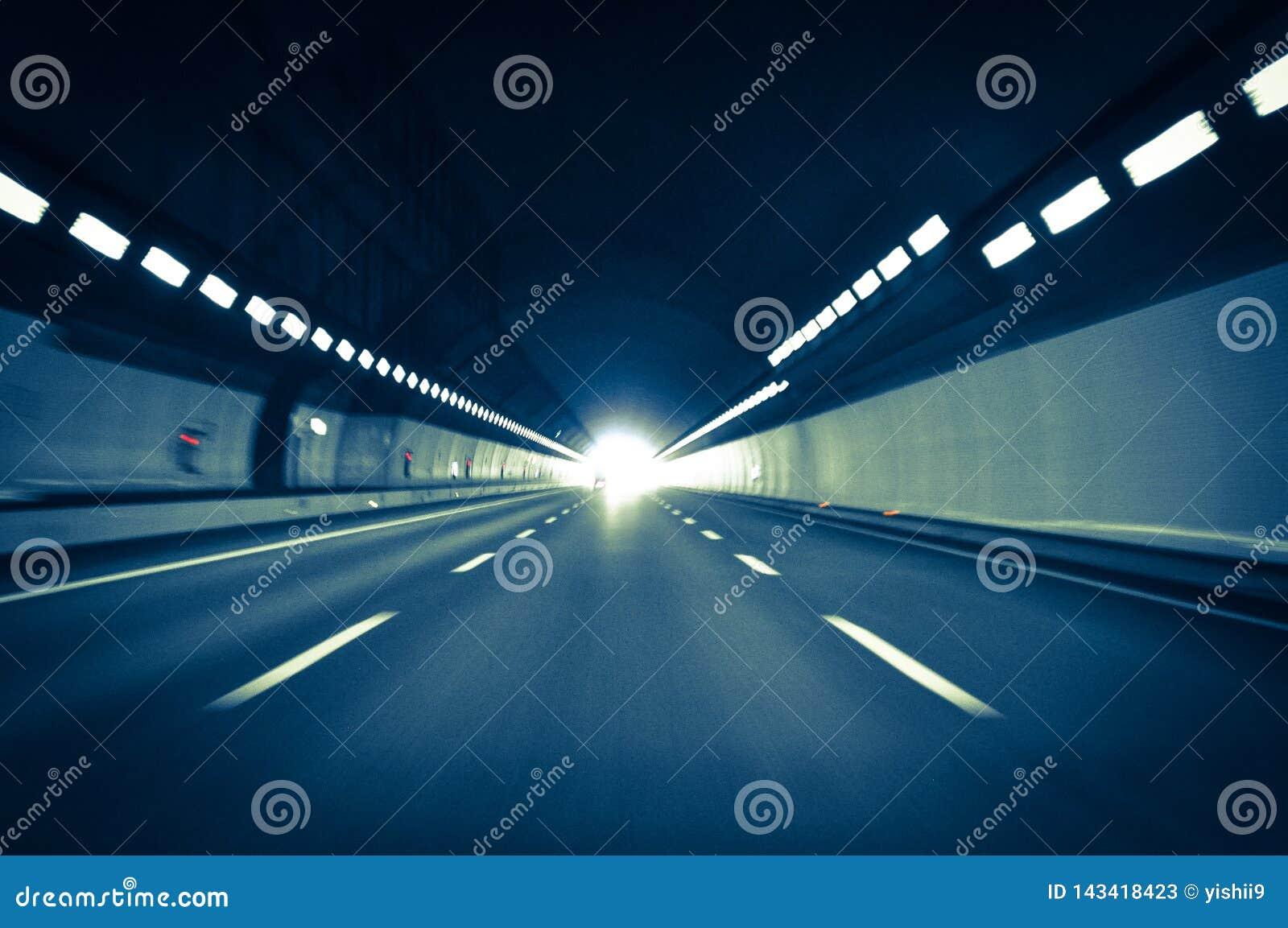Körning på den hög hastigheten i en tunnel på en huvudvägväg