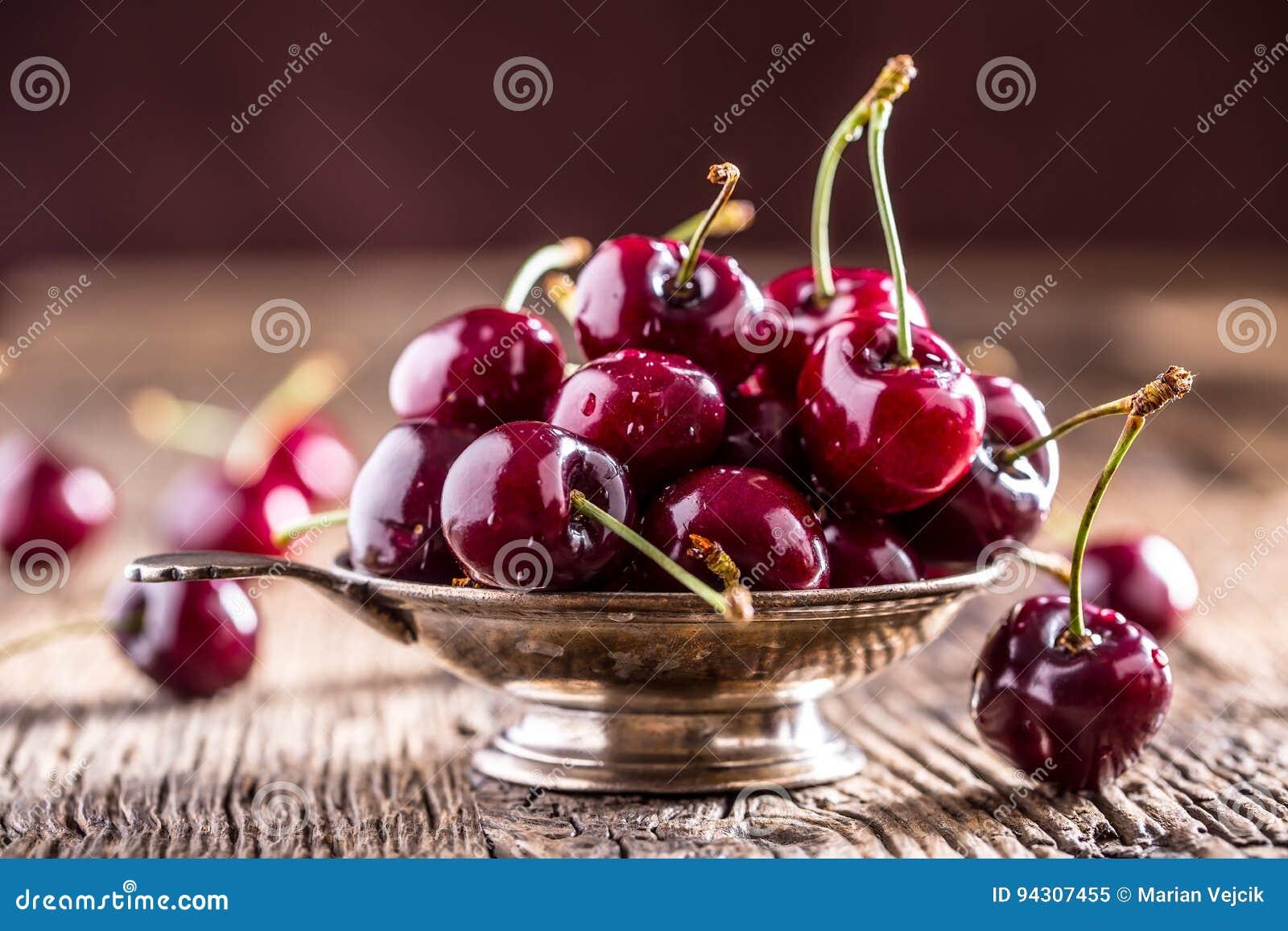 Körsbär ny sötsak för Cherry Läckra körsbär med vatten tappar i retro bunke på den gamla ektabellen