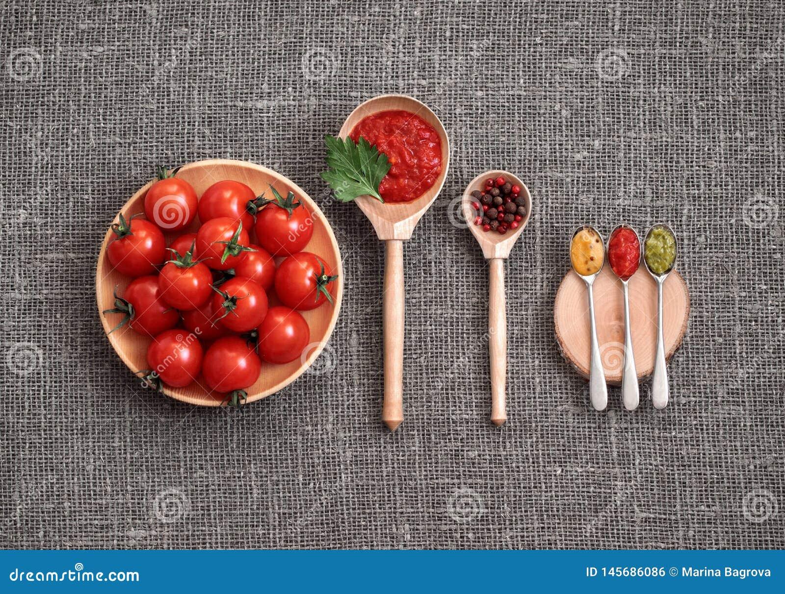 Körsbärsröda tomater i en träplatta på en grå bakgrund Adjika sås, rött och svartpeppar, persilja, senap och pesto i skedar
