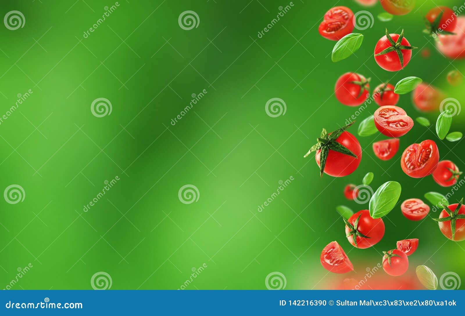 Körsbärsröda tomater och sidor som faller från luften