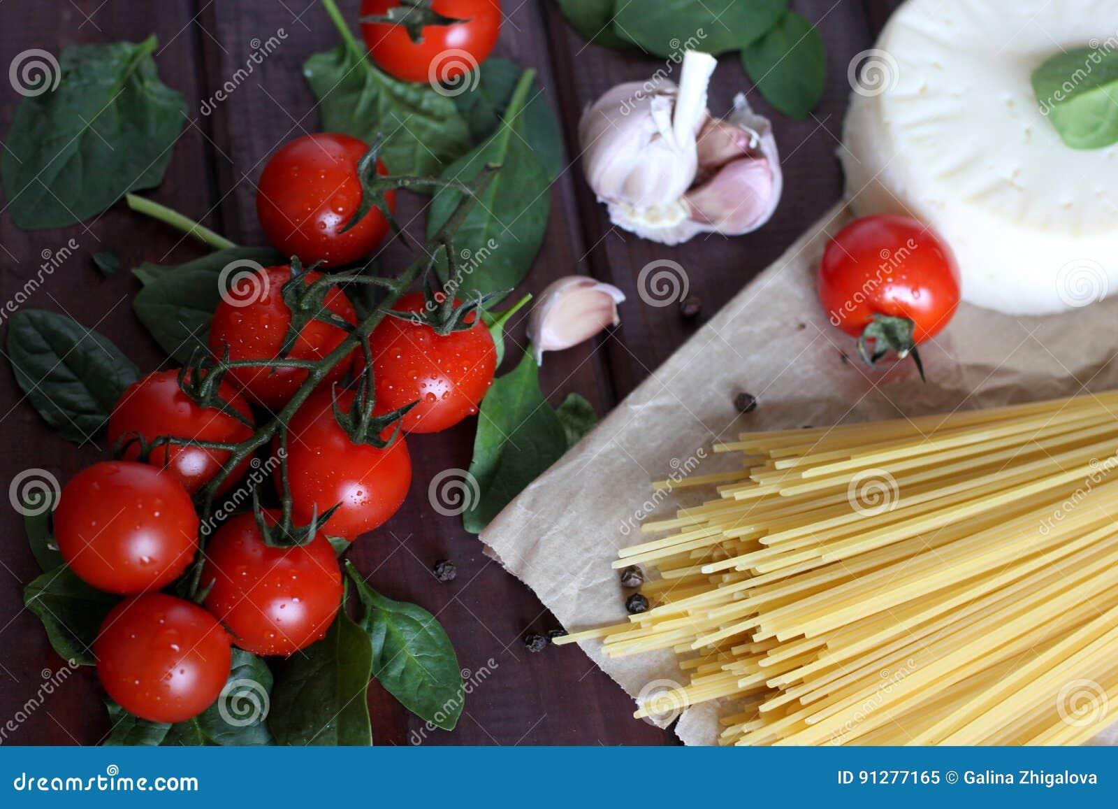 Körsbärsröda tomater, rå pasta, vitlök, spenat på mörk wood bakgrund
